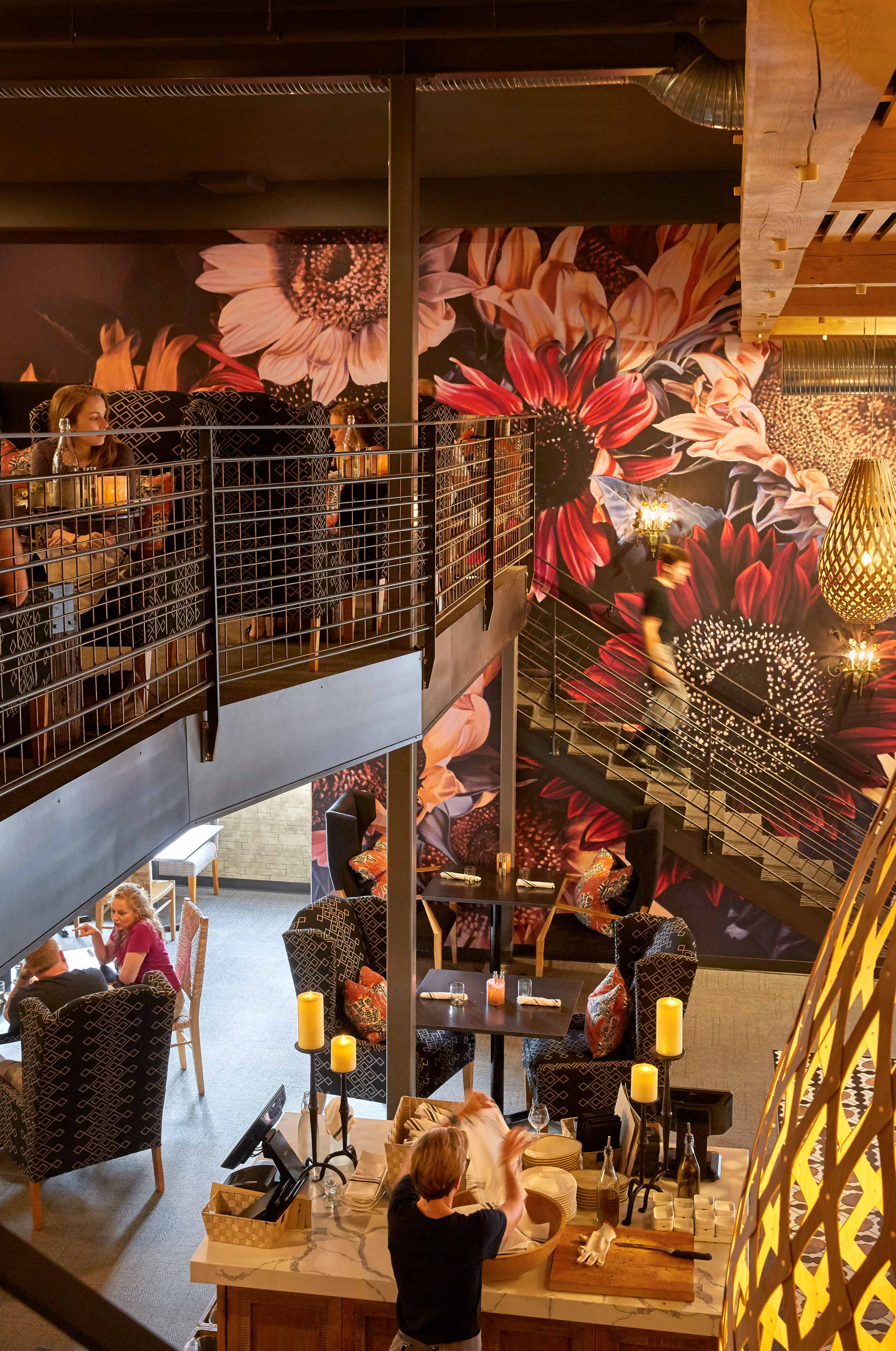 One of the two staircases accessing the mezzanine is flanked by a mural of over-sized sunflowers done in unexpectedly moody jewel tones.