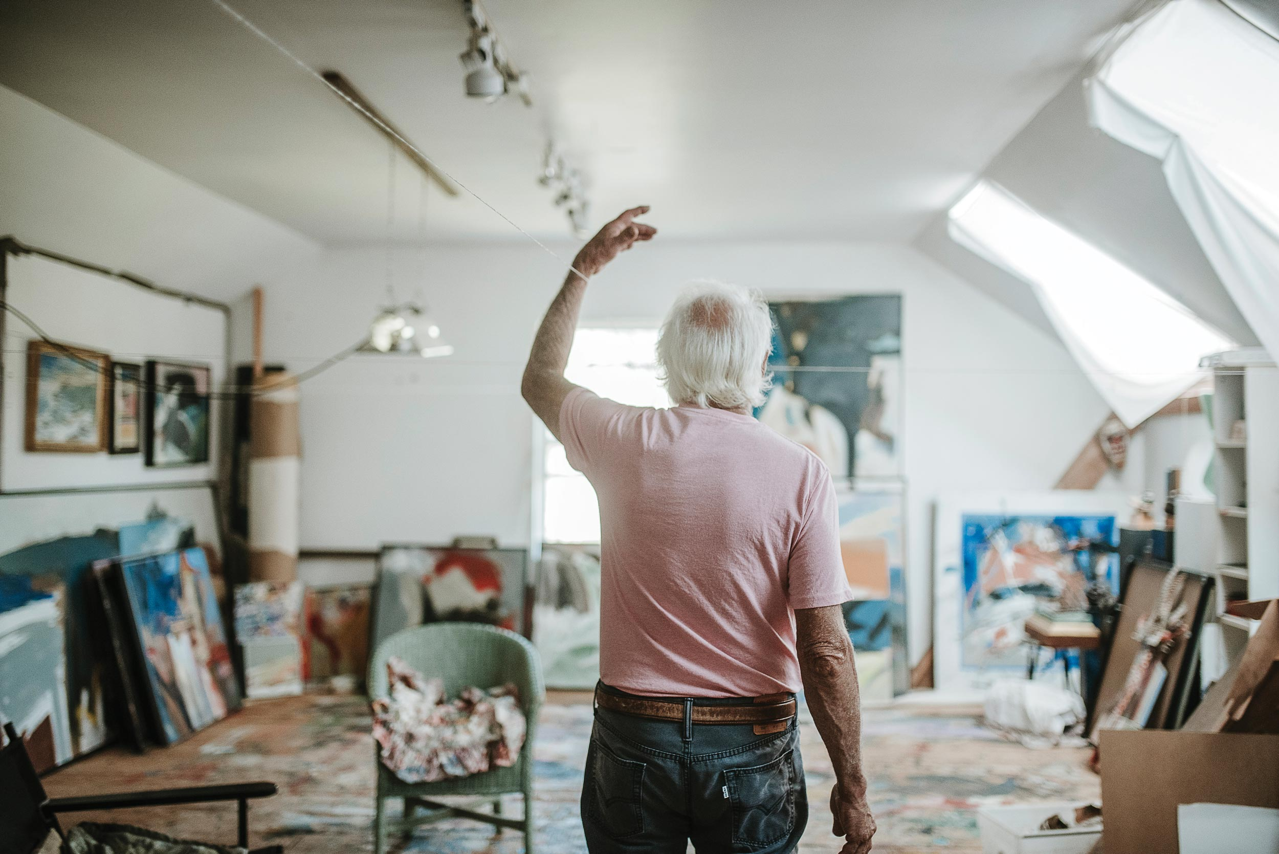 Denis uses string stretched across the length of his studio to guide and orient himself. The studio is lined with his completed paintings as well as Denis's found-art sculptures and other inspiring keepsakes he has gathered over the years.