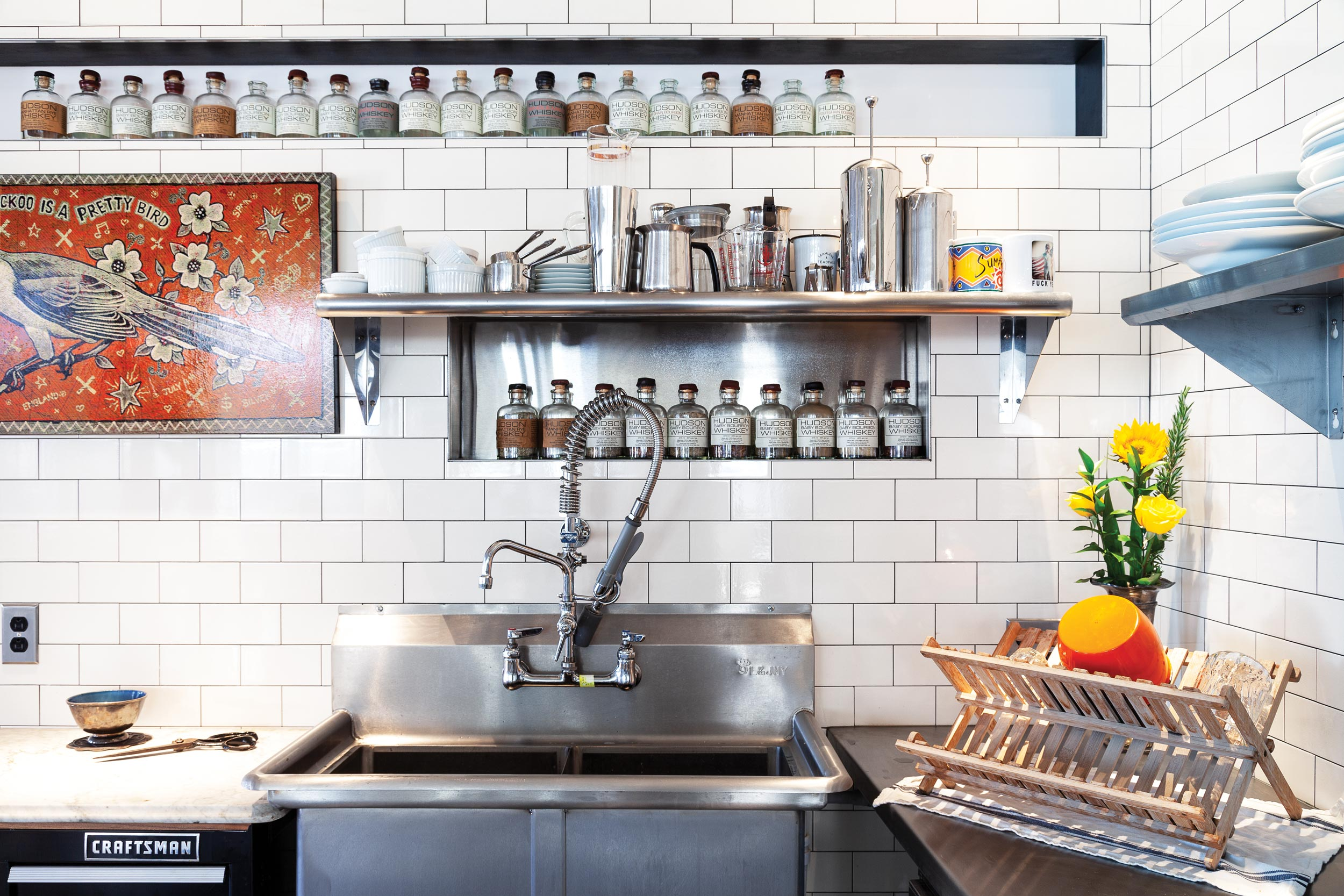 Keon didn't want upper cabinetry in his kitchen, but he did want his spices stored in former bourbon bottles on narrow shelves or in nooks. The bird painting is by musician Jon Langford.