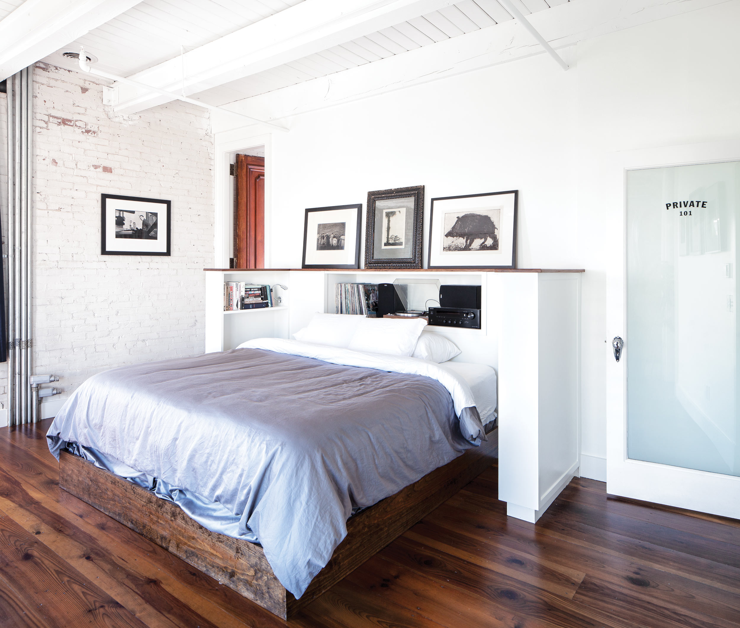 Keon told cabinetmaker Paul Lewin that he wanted to listen to music in bed, so Lewin built this bed nook to house his stereo and serve as a record cabinet while also displaying art like the etching of a pig by Tom Cornell and a 1923 William H. Bettle silver gelatin print of a luxury liner.