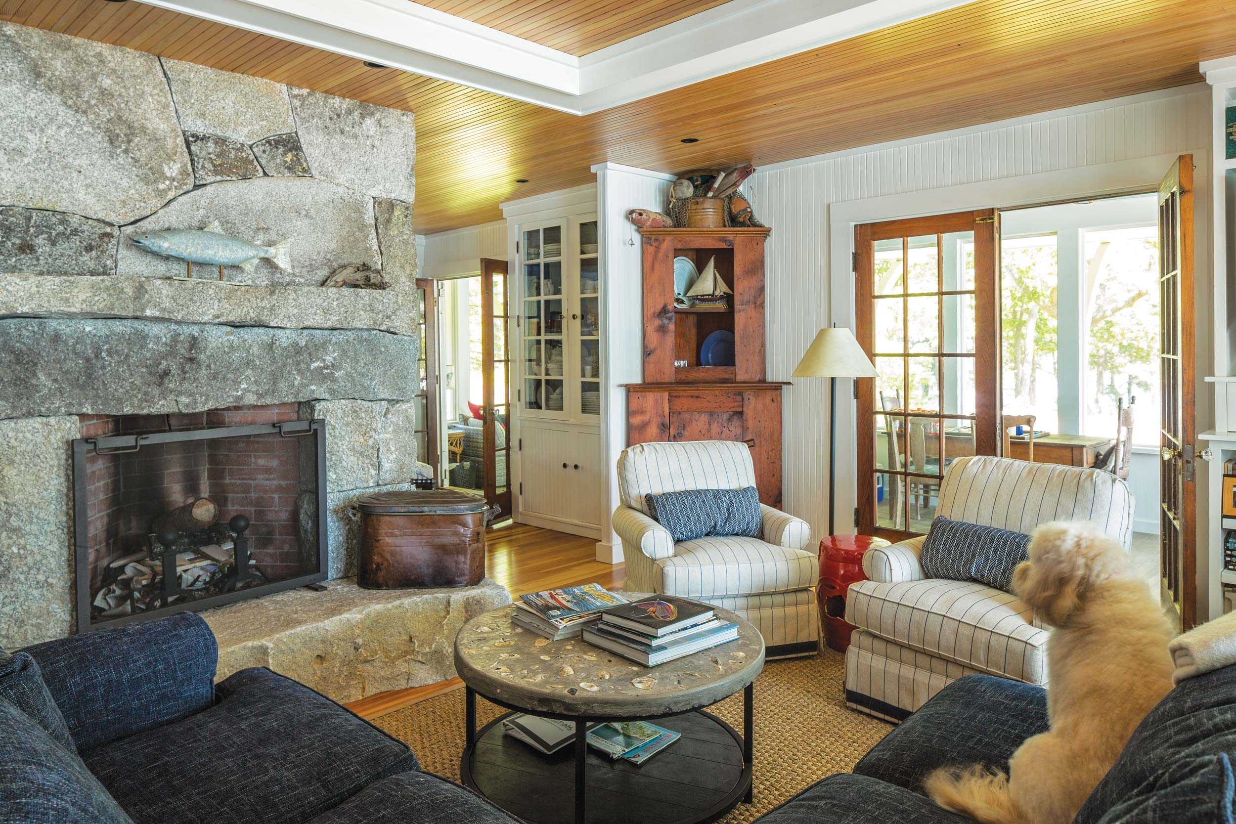 The massive living room fireplace is made of local granite and separates the living and dining room. The corner cabinet and Douglas fir ceiling are original. A new, non-structural white beam is intended to define the space.