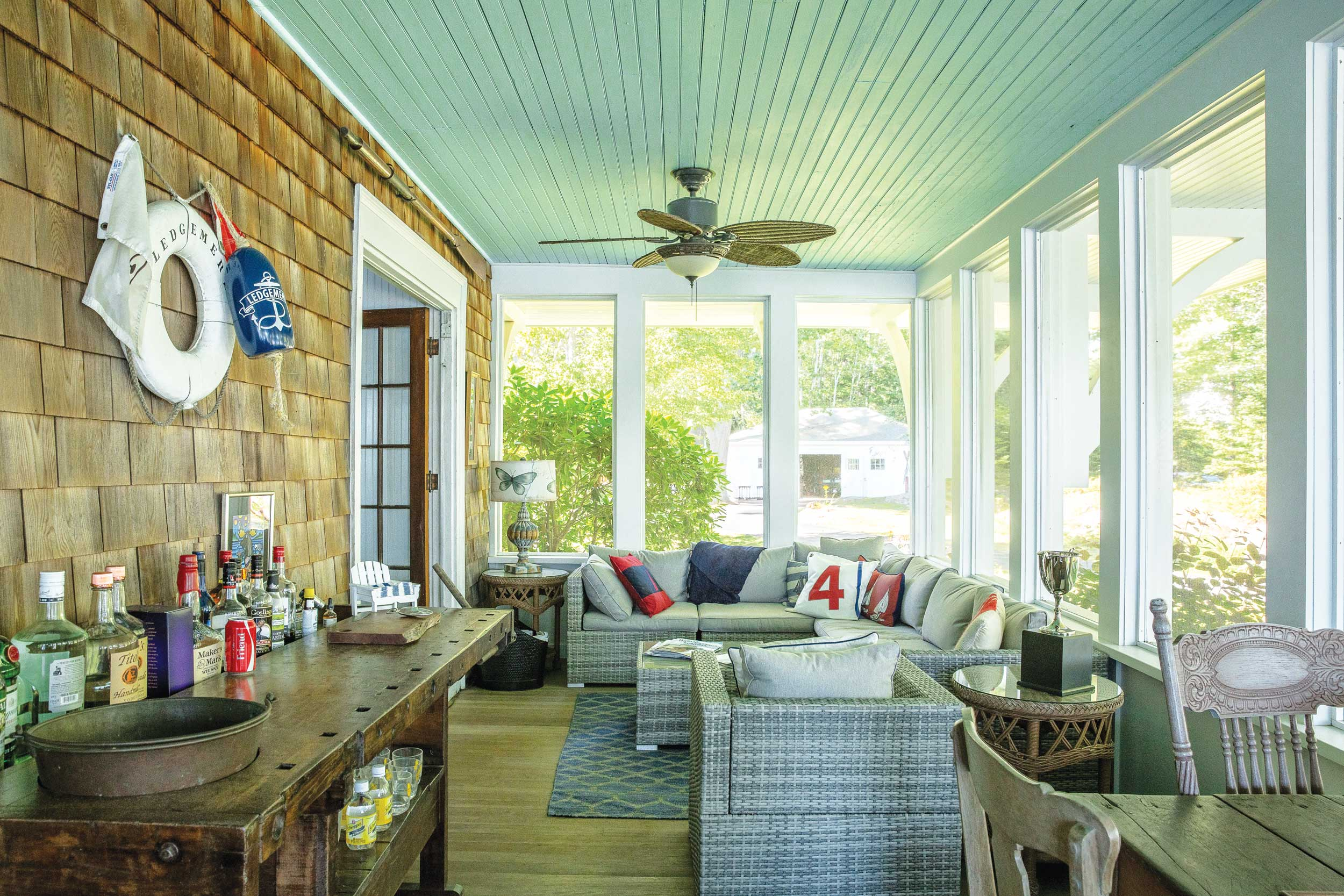An enclosed porch with a yacht club lifesaver, bar area, game table, and blue ceiling, the latter a custom in South Carolina (where the tradition seems to have to do with warding off evil spirits) and in New England (where the custom may have to do with fooling insects into not building nests.) Other theories about why people paint porch ceilings blue? It resembles the sky.