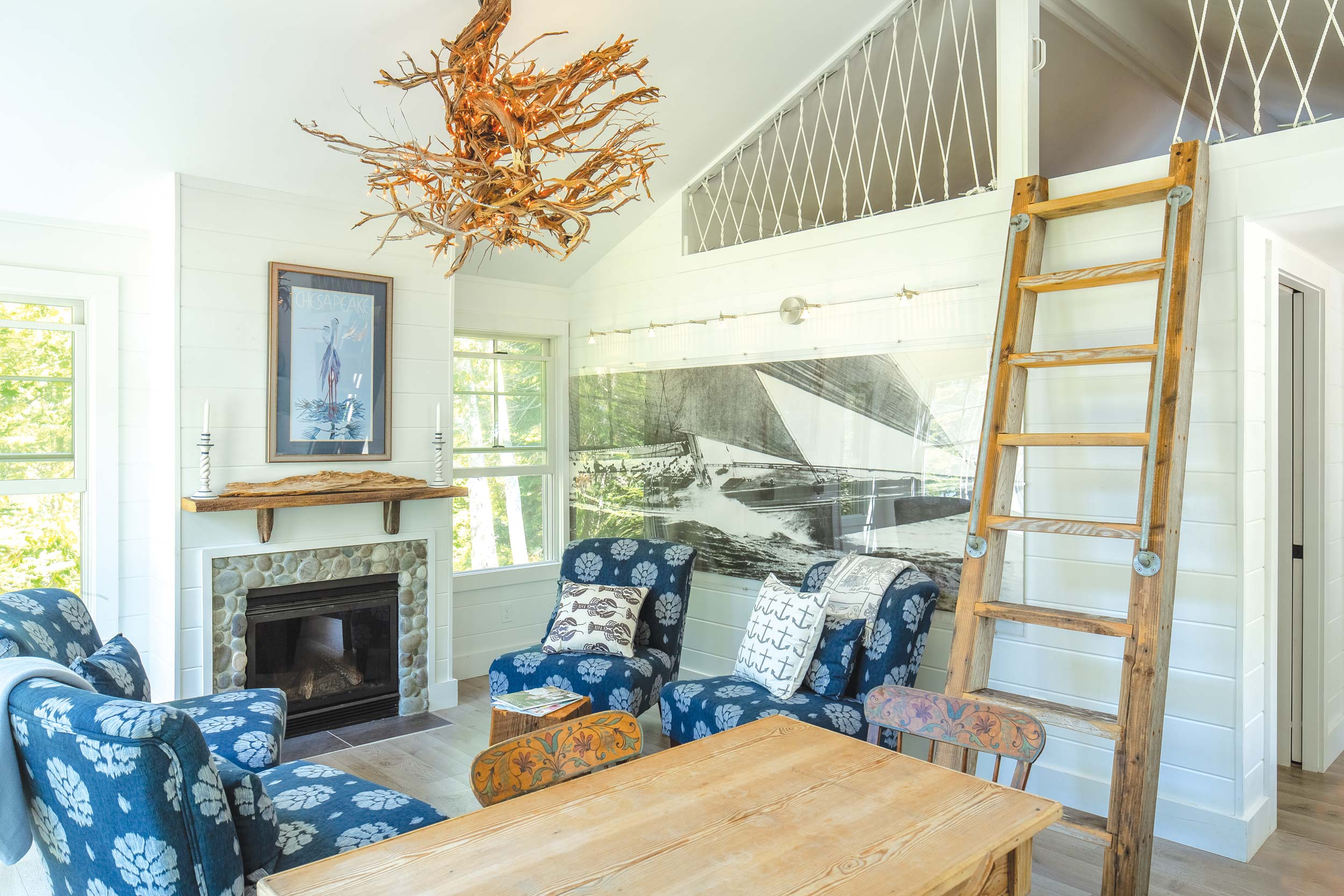 Doug used pieces of an old dock to make a ladder to the guest room loft, which has rope attached to boat cleats in lieu of conventional railing. The fireplace mantel is made from materials found on the beach, as is the stone fireplace surround.