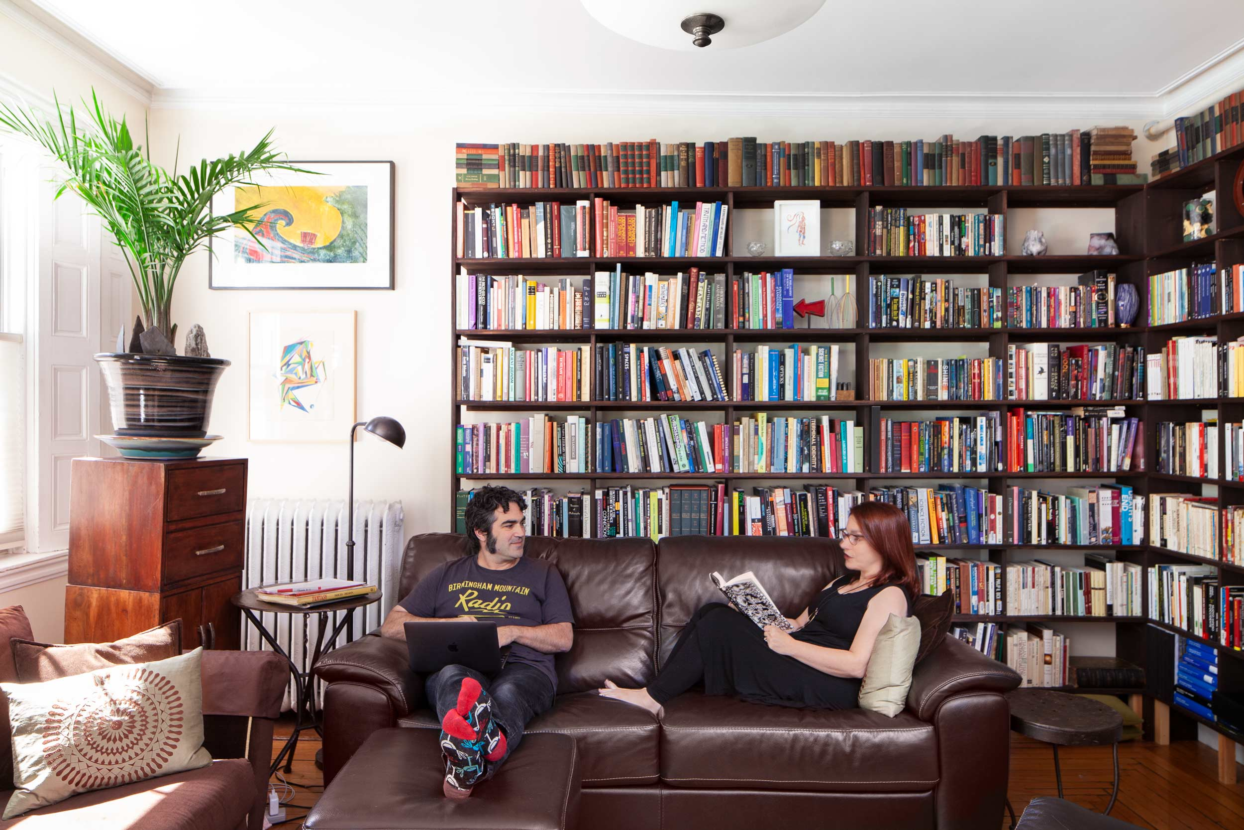 """As they rest on their living room's espresso leather couch, Montanaro and Saiber are surrounded by bookshelves built by Montanaro. They call the wall behind them and to the left """"The Dads' Wall,"""" because the top print was made by Kavi's father, Tony Montanaro, and the bottom painting by Saiber's biological father, Robert Saiber, who died when she was just 19 months. The wood drawers are from Asia West."""