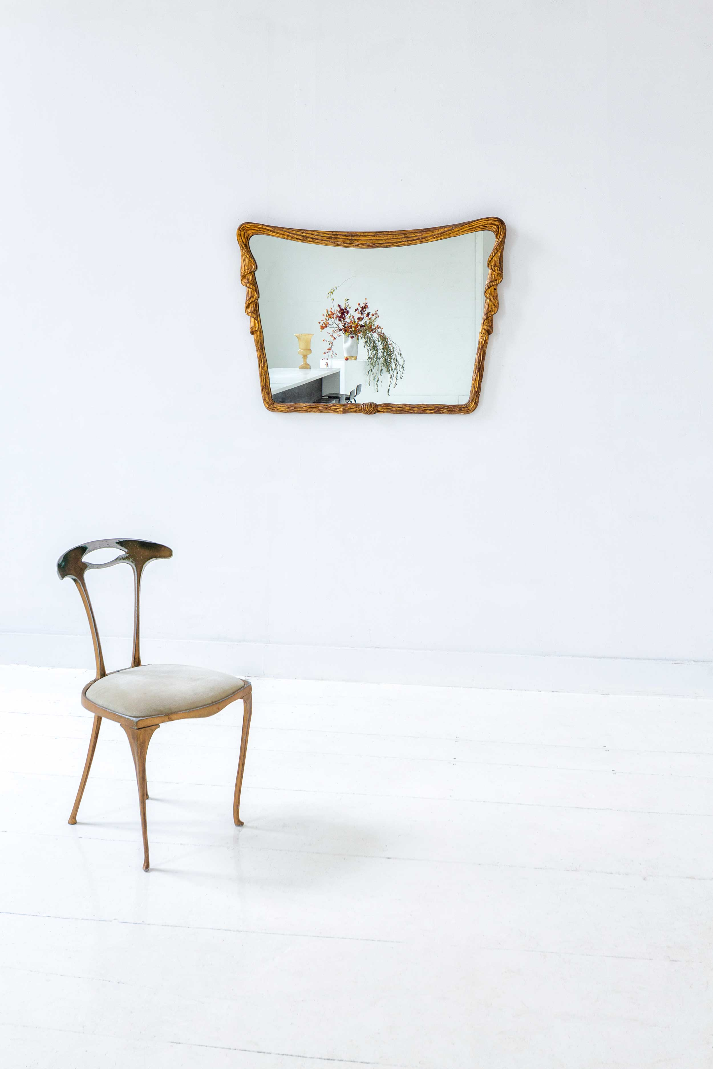 In the common room, an antique mirror and chair share the space with modern art.