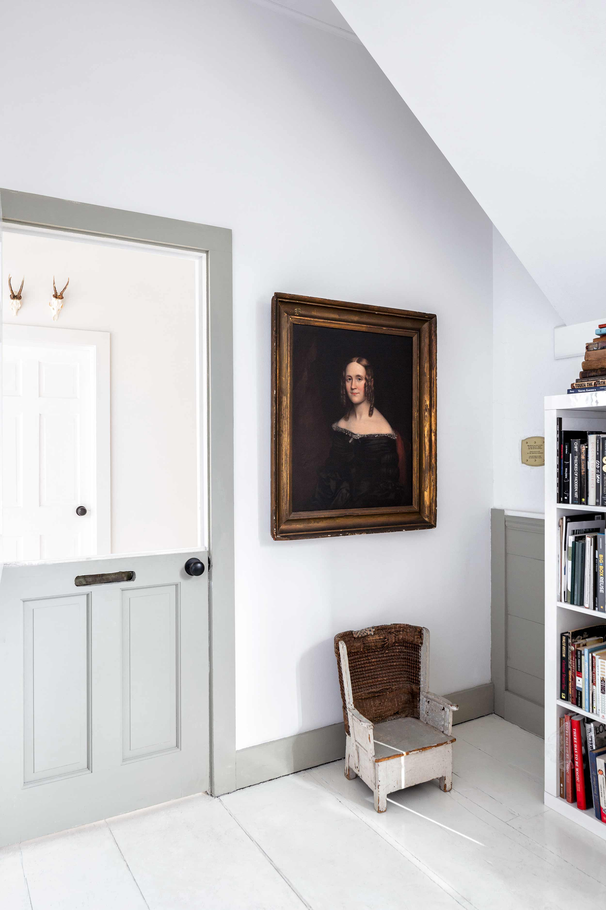In the reading room, an antique Dutch door with mail slot. The portrait is of Clarissa Pear, the distant relative of a college friend. Below is an antique child's chair.