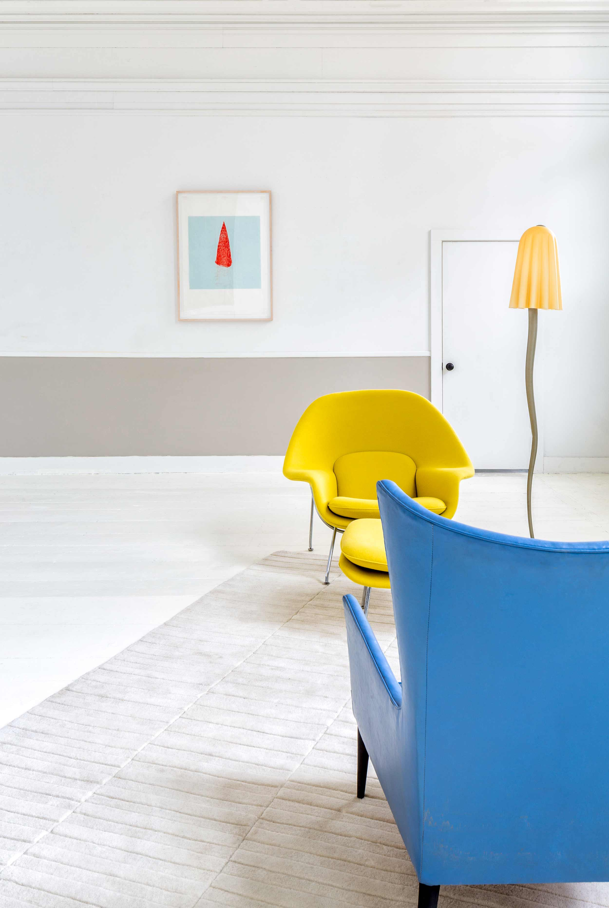 In the living area, a womb chair by Eero Saarinen McNeil had reupholstered in vintage Knoll fabric. The blue chair is midcentury Danish. The lamp by Vetri, from the 1970s, has a Murano glass shade. The rug is by Angela Adams.