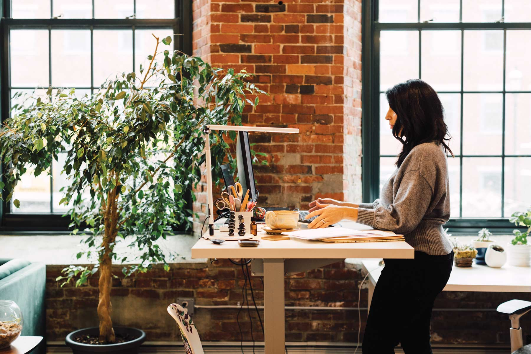 Zoulamis, at her desk, which enjoys a view and the company of many plants.