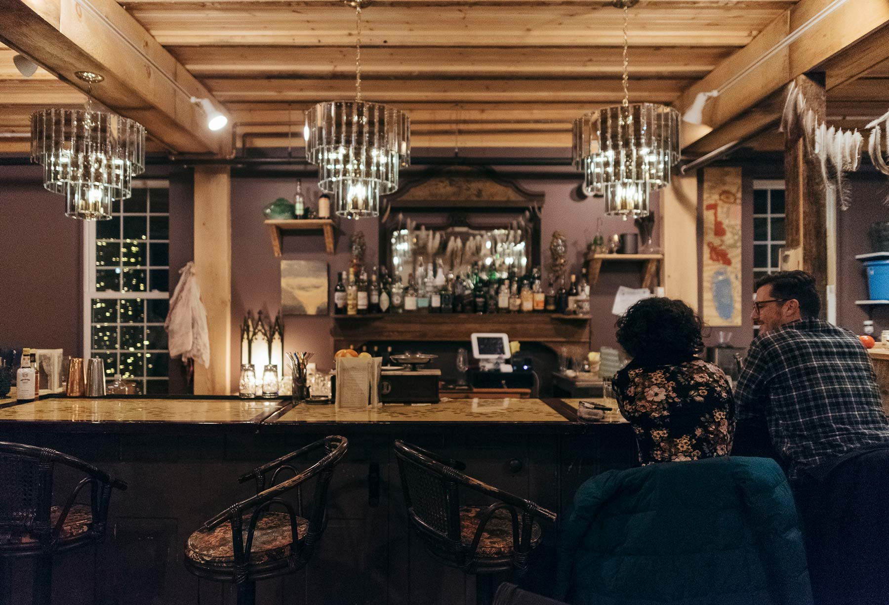 Vintage chandeliers glow, part of the warm atmosphere at Vessel and Vine.