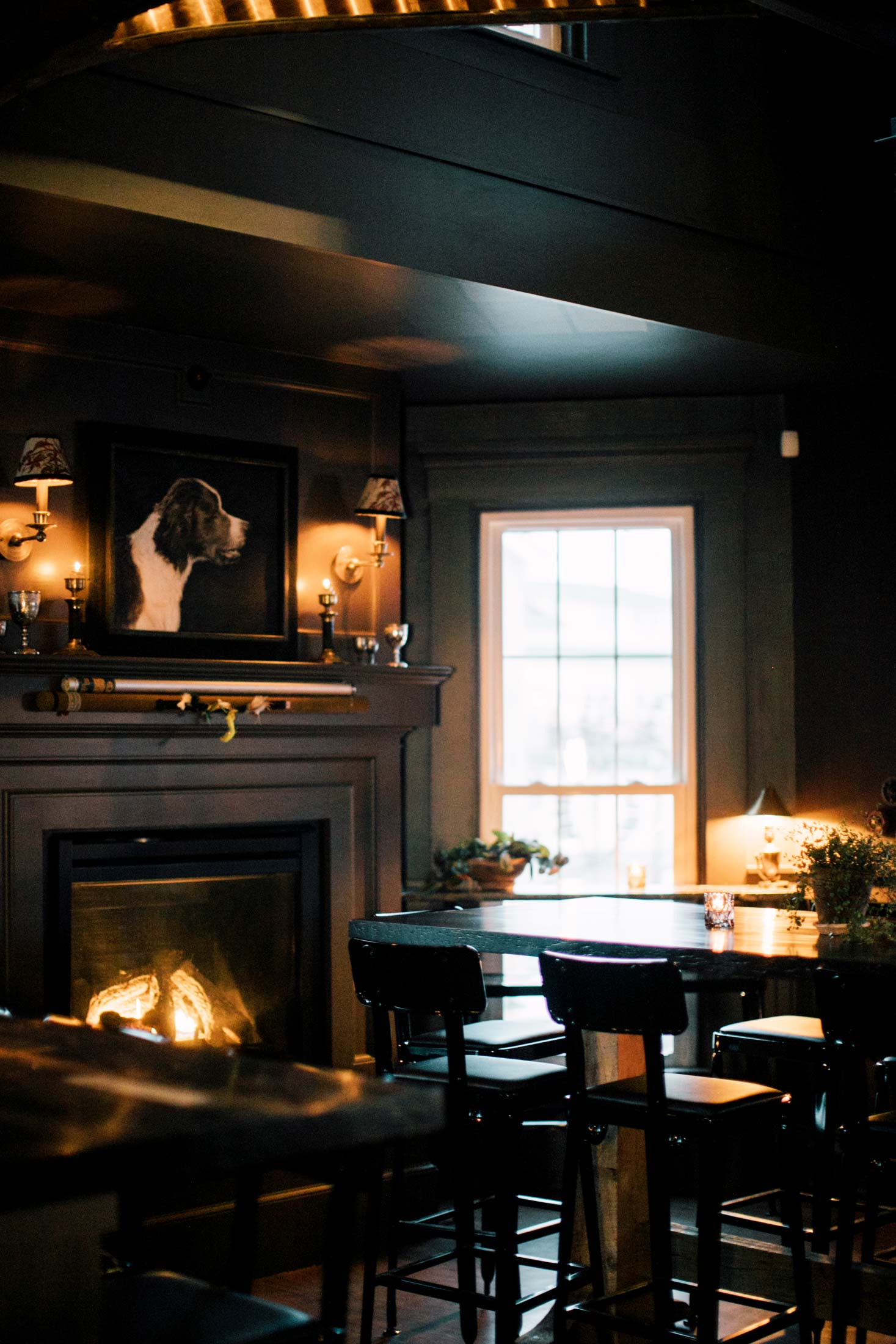 In the tasting room, vintage fly rods in their cases decorate the mantelpiece. The tables are made from old cask wood by River Drive Cooperage, and the painting of the pointer above the mantel is by David Edward Allen.