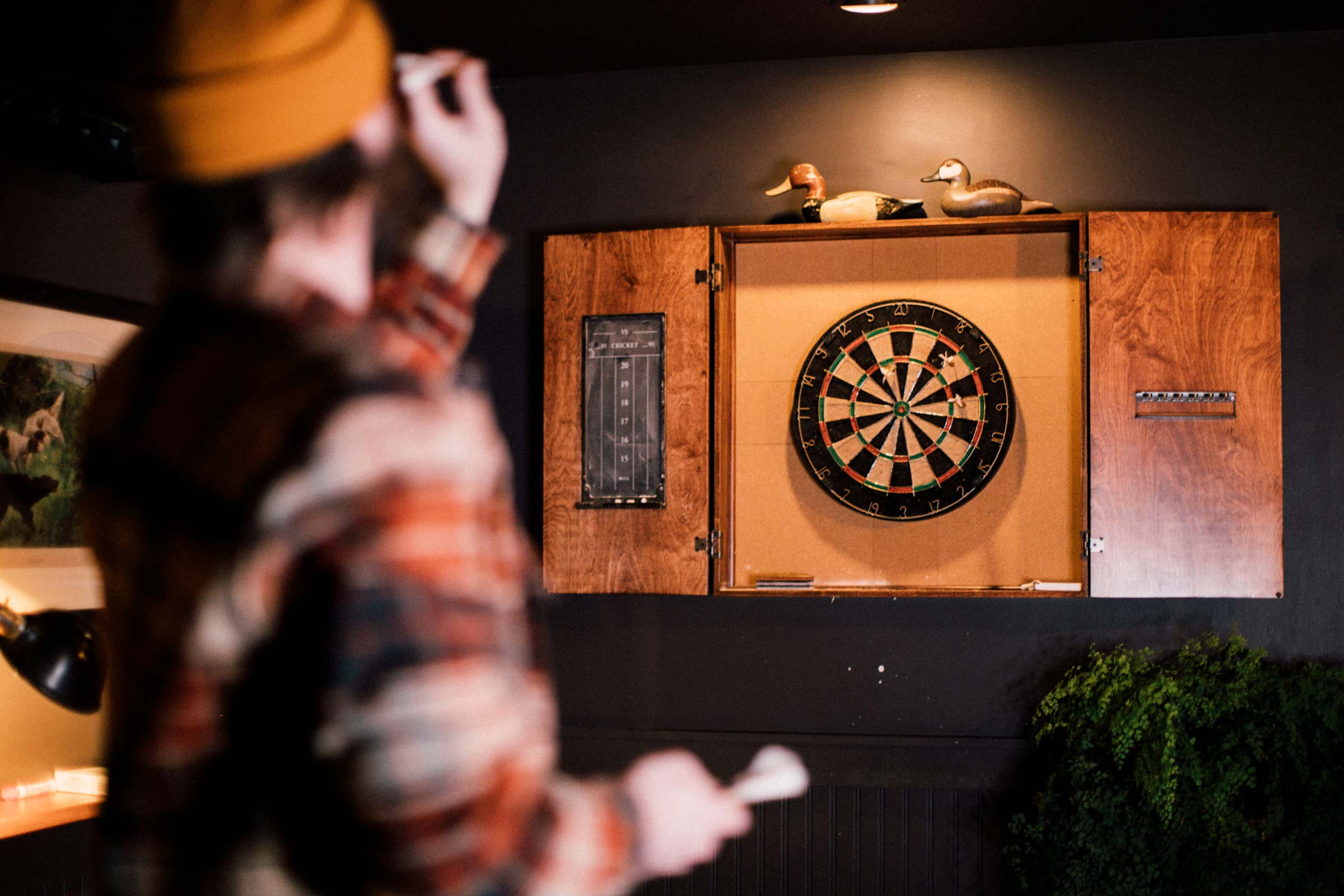 Enjoying a round of darts in the game room upstairs.