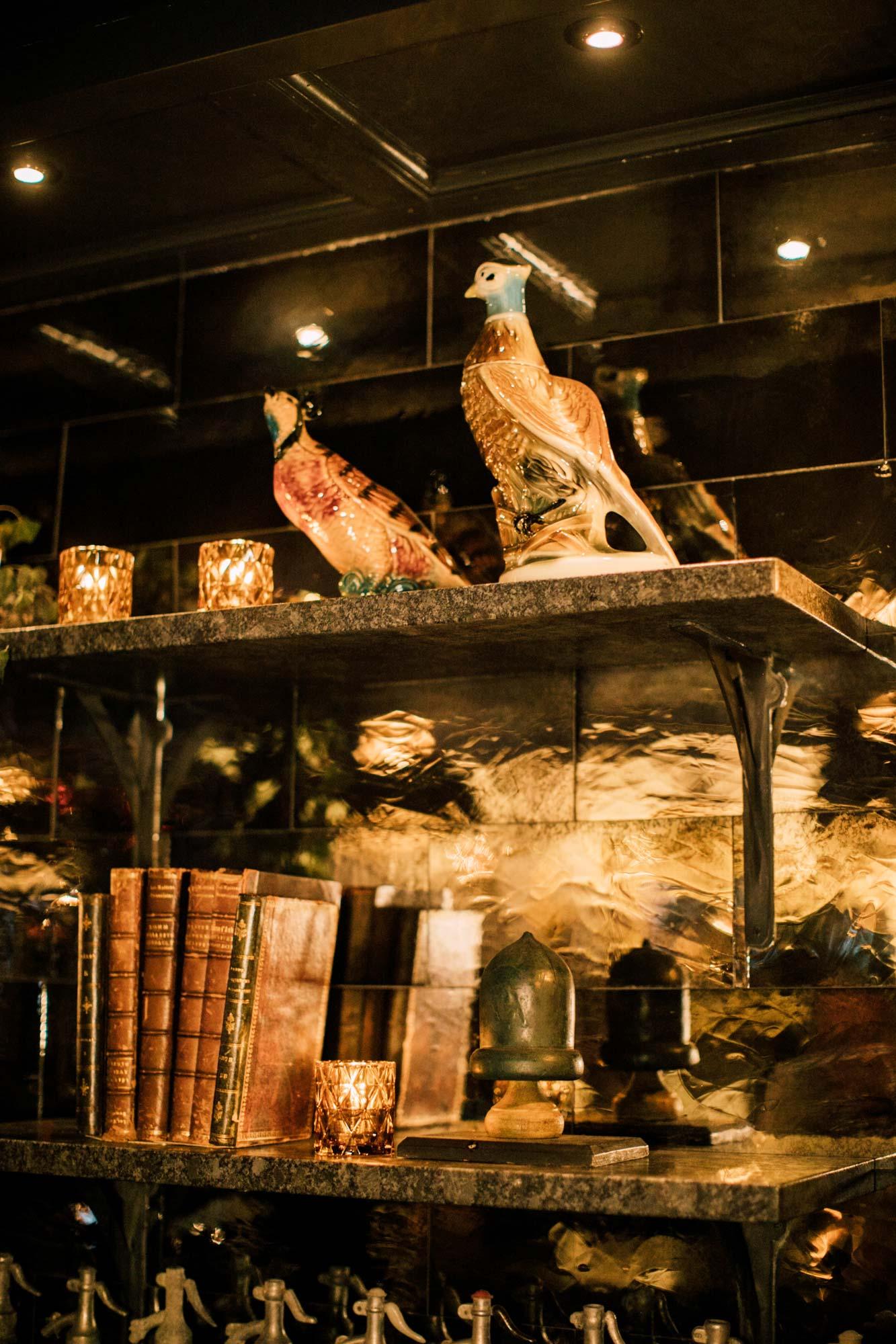 A pair of vintage porcelain pheasants perch on the back bar. Mirror tile is by Distinctive Tile & Design.