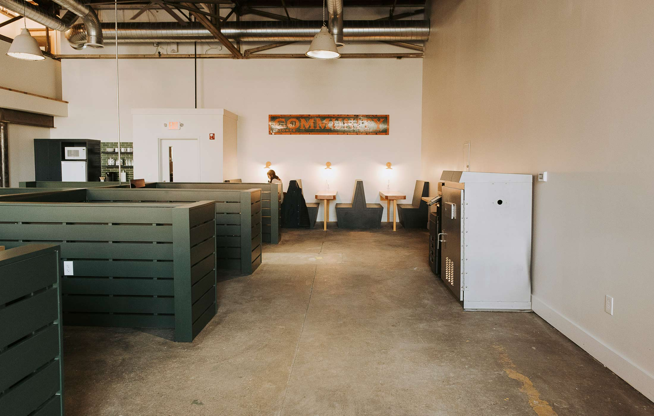 "The Public Works' communal workspace features private offices, open studios, and floating desks. The metal cabinet on the right is a former traffic signal controller and now contains printing paper and supplies. The vintage industrial pendant lights are from Halogen Particle. The ""Community"" sign was found at Portland Flea-for-All."