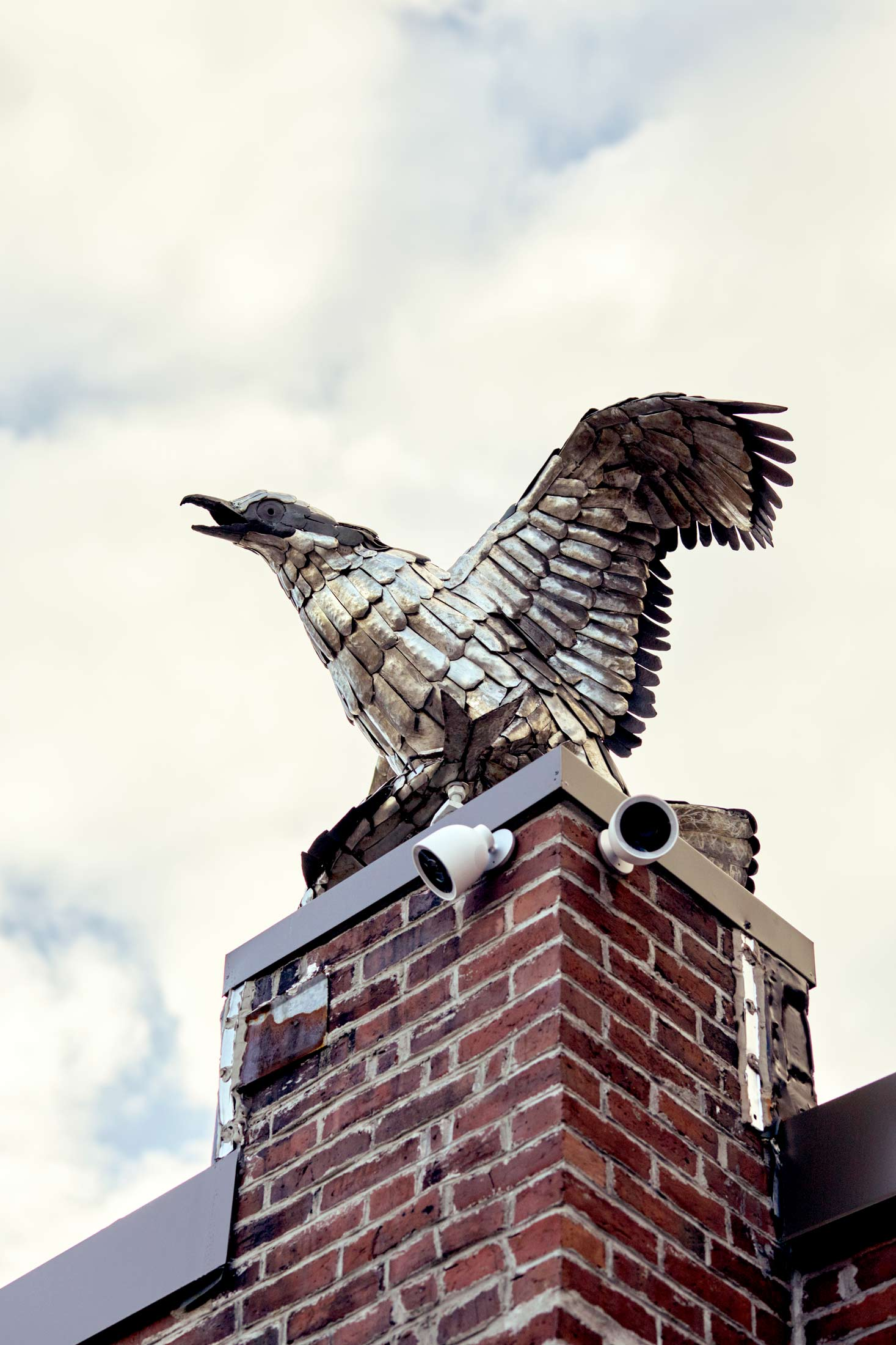 An osprey eating a fish perches on a non-functional chimney. Lauren's father did the sculpture.