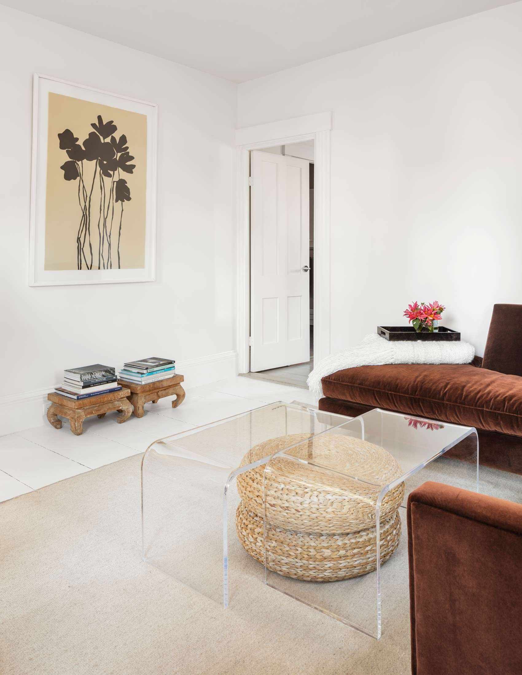 The mix of items in the living room includes two acrylic tables offset for interest, a rattan foot stool from IKEA, and teak Indonesian prayer stools. The black ink painting is by Susan Havel Smith.
