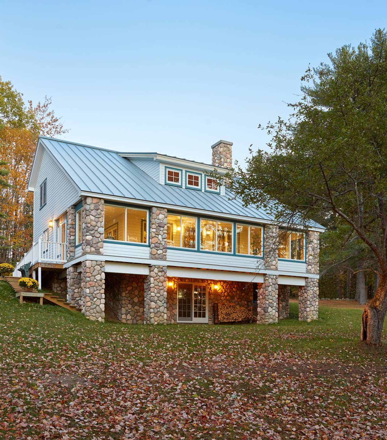 An outdoor shot of the lake house provides a look at its Hardiplank exterior and fieldstone pillars and foundation. The glassed-in porch ensures that the tranquil lake view can be enjoyed in all weather.