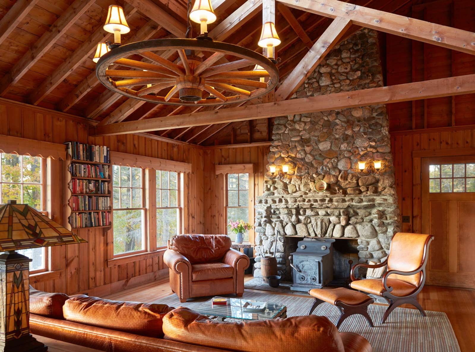 """A picture of the original lake house provides a glimpse of the unique """"friendship fireplace"""" built with stones from all over the world. In the new lake house, Kaufman wanted to reproduce as many beloved details as possible, allowing for stylistic updates to keep things familiar but fresh."""