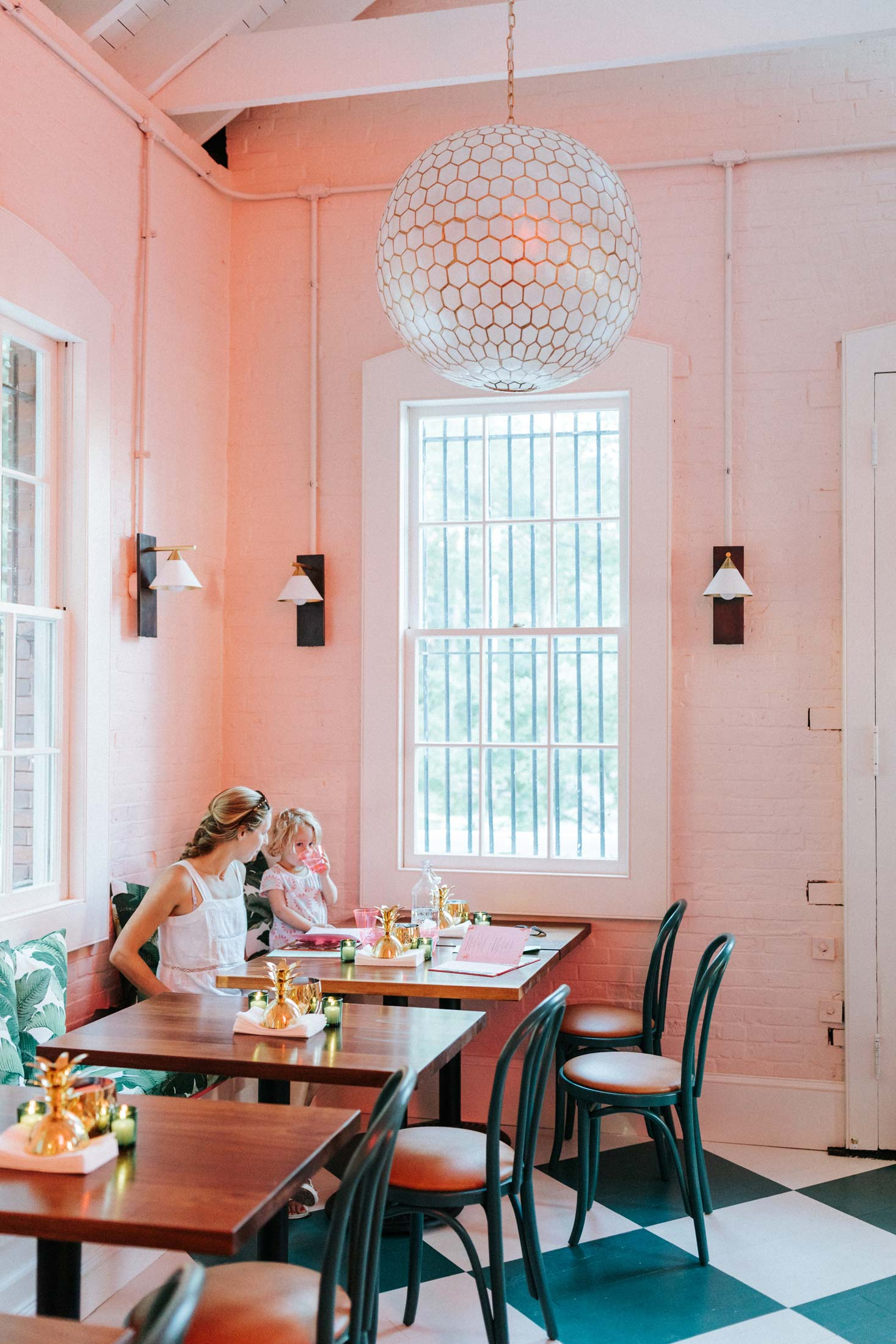 In the dining room, mahogany tables by Atlantic Hardwoods in Portland are flanked by banana leaf fabric banquettes and custom painted chairs fitted with ostrich leather cushions, from The Chair Market in Brooklyn. The wall sconces, chosen by Wight to anchor the airy space, are by Kelly Wearstler for Visual Comfort. The gold pineapples on the tables have a practical purpose in addition to island charm: They hold Wet-Naps, Wight says, as much of the menu is meant to be eaten by hand.