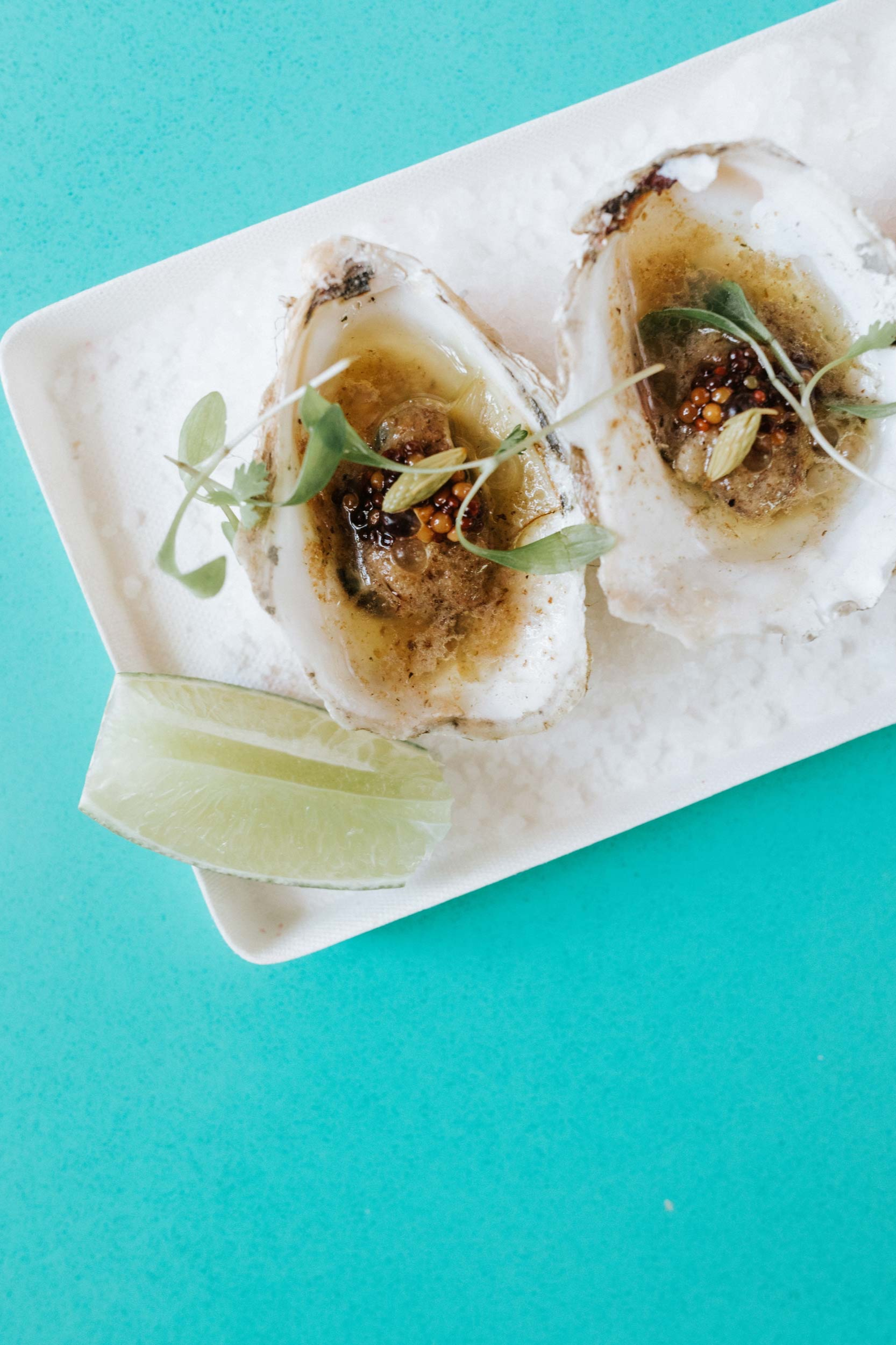 There are several ways to enjoy oysters at Crown Jewel. Above: Grilled oysters with umami butter, yuzu pearls, and pickled mustard seed.