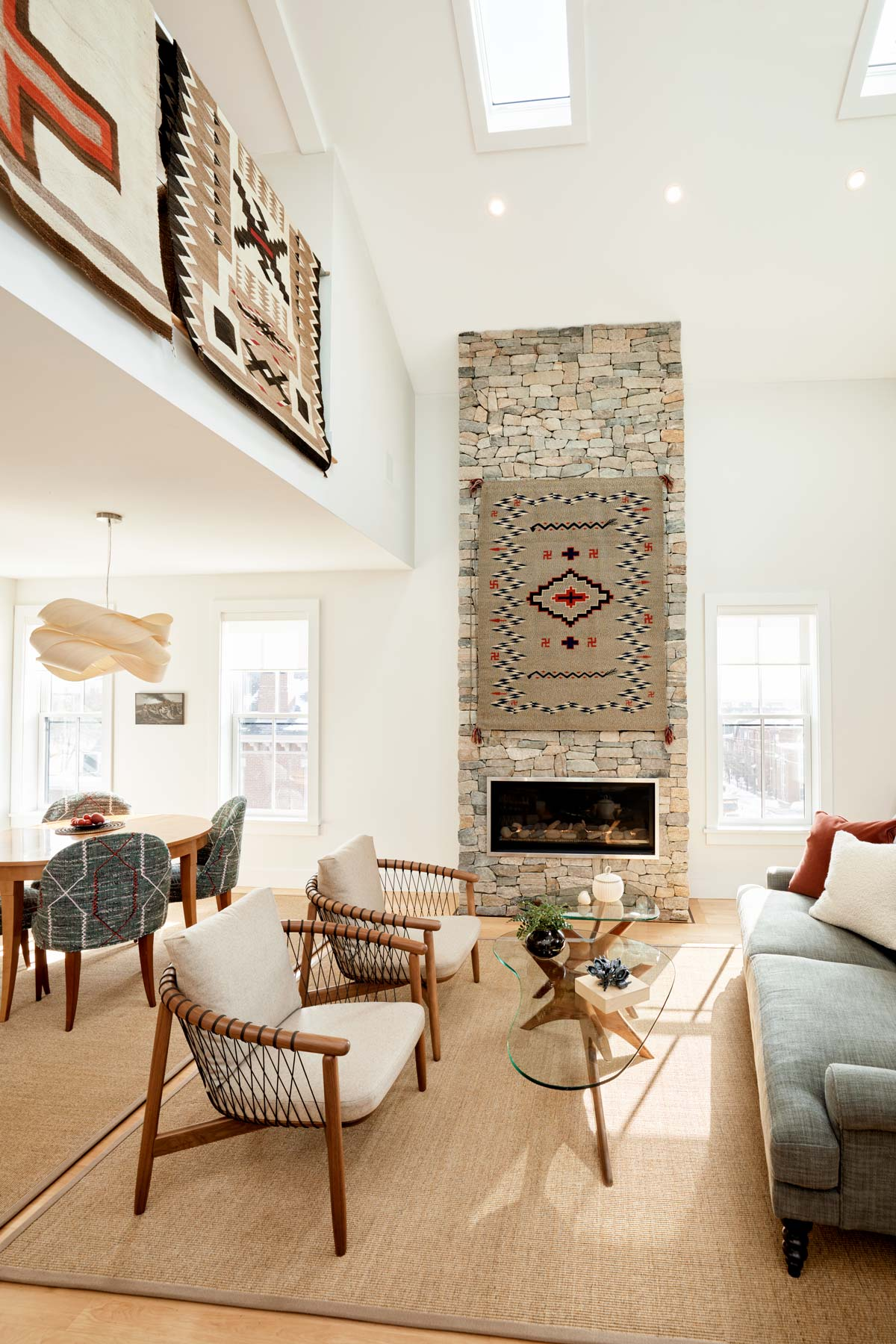 Interior designer Ariana Fischer paired new, parachute-corded chairs in neutral tones with Werber's midcentury modern, glass-top tables to give the seating area an open, airy feeling and highlight the Navajo weaving hanging over the fireplace.