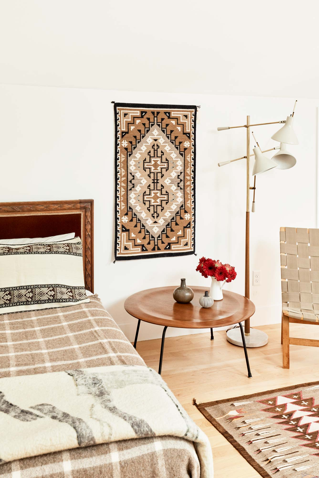 A traditional, 19th-century bed sits alongside mid-century modern furnishings in Werber's office. Navajo textiles throughout the room tie the eclectic mix together.