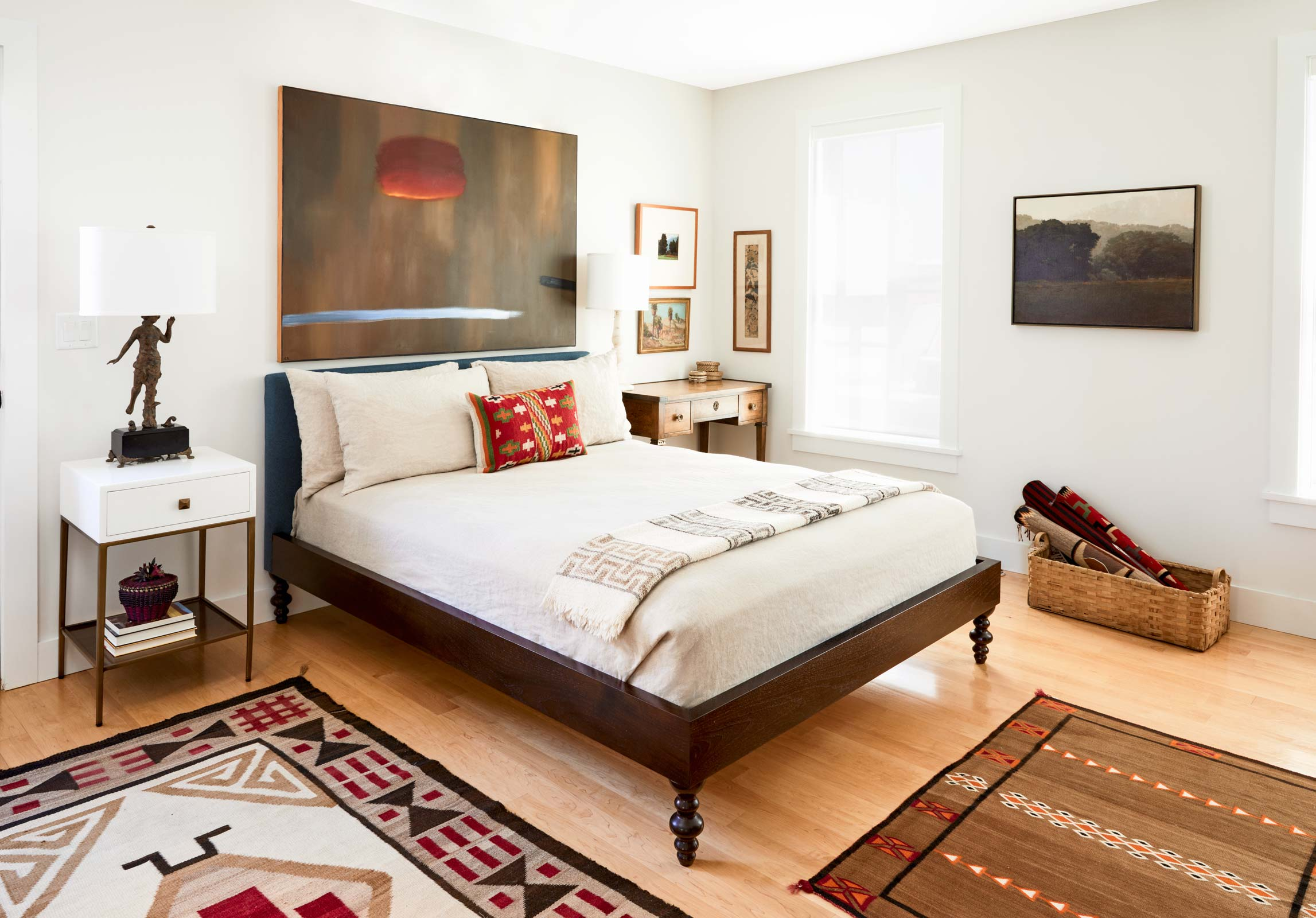 An heirloom writing desk and dancer lamp inherited from Werber's mother adorn the master bedroom, which also features paintings by Los Angeles artist Curtis Ridley (over the bed) and Seattle artist Marcus Bohne (above the basket).
