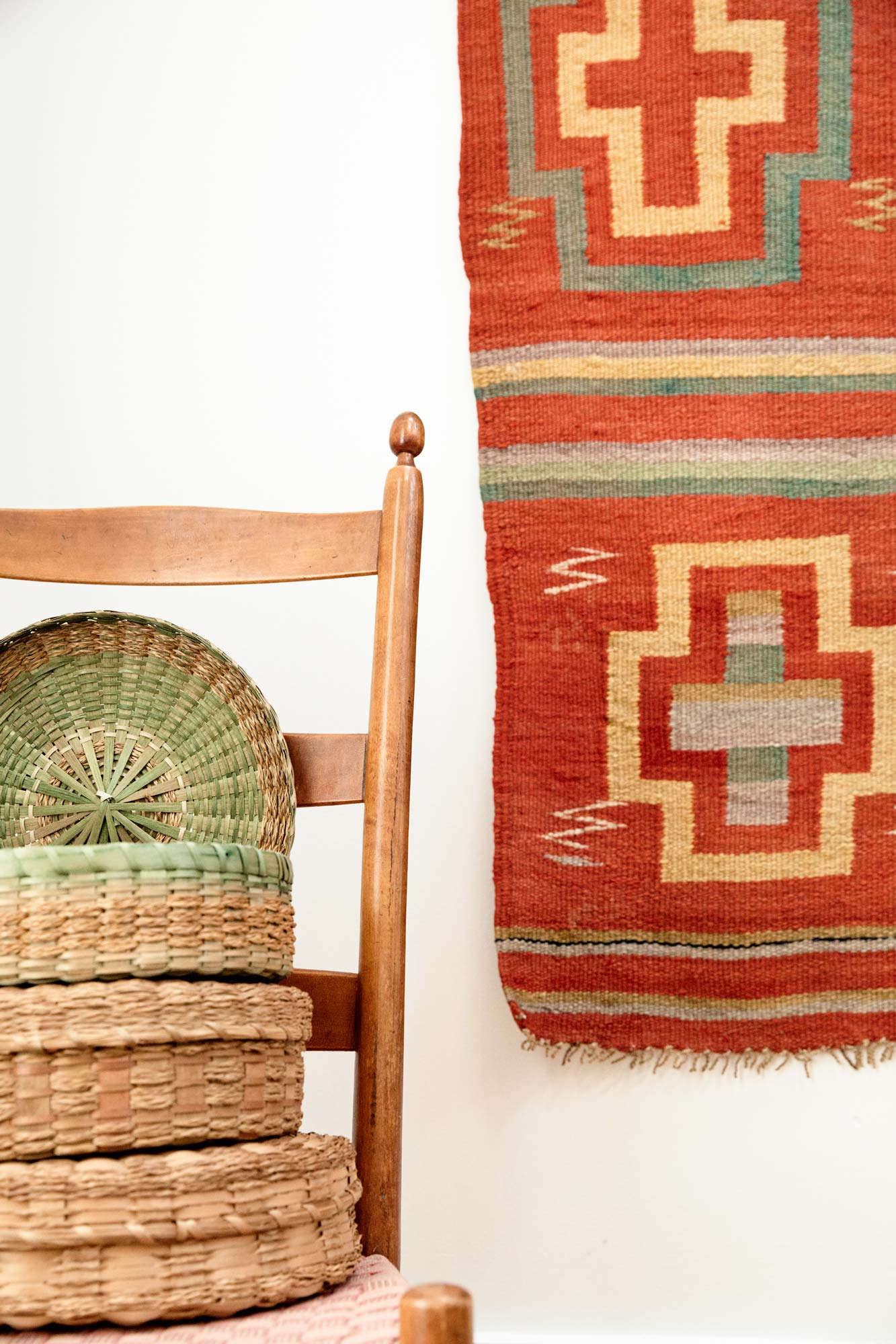 "1950s-60s Maine Wabanaki ""flat"" baskets, made from braided sweetgrass and dyed brown ash, sit atop a 19th-century Shaker child's rocker in the main living area. A rare Zuni blanket circa 1880 hangs on the wall."