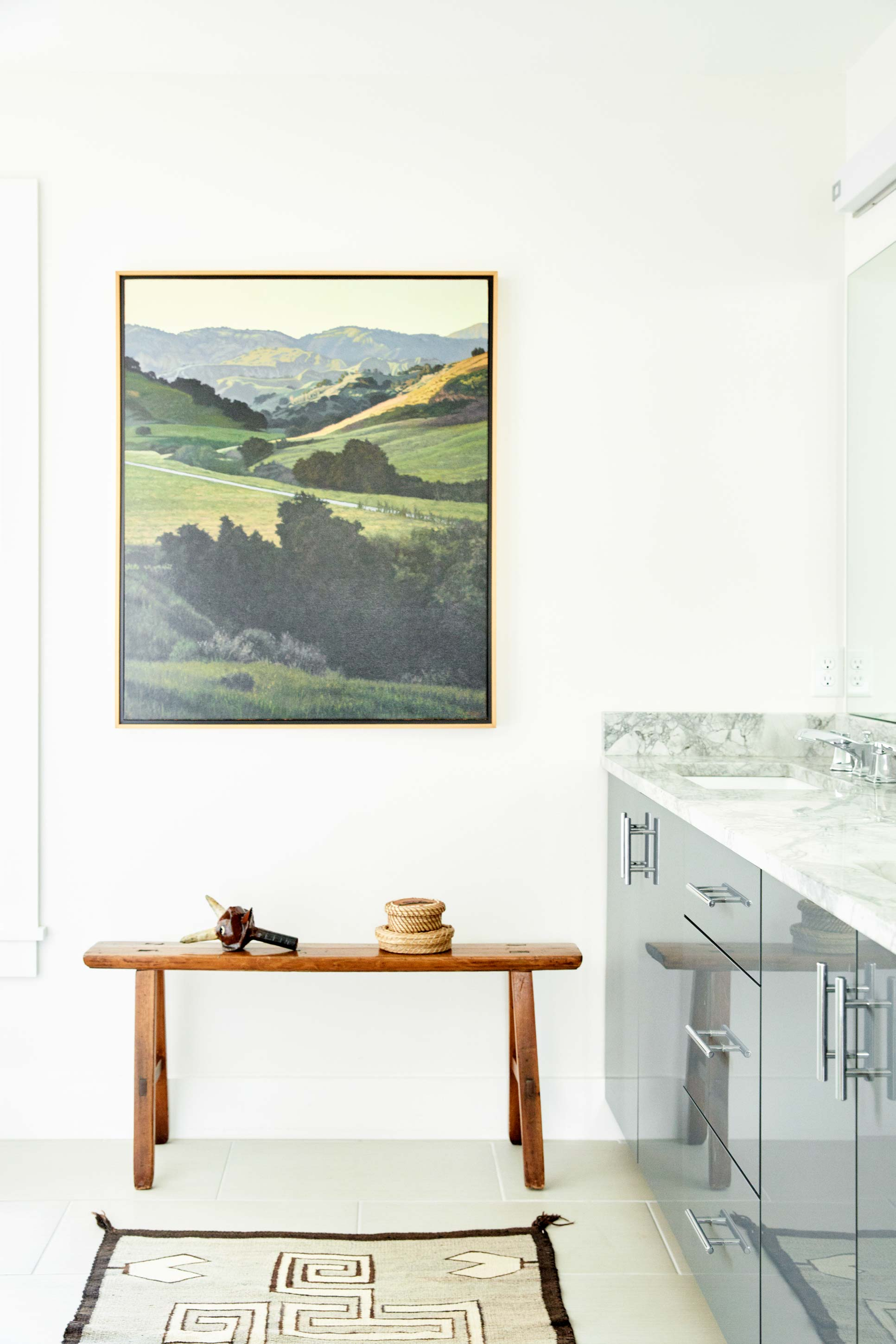 A curated spot in the master bath features a painting by Bruce Everett over a French nun's prayer bench from the late 1700s. On the bench is a Krampus by E. Michael Contreras and two Wabanaki baskets topped with porcupine quills. A circa-1920s Navajo weaving completes the look.