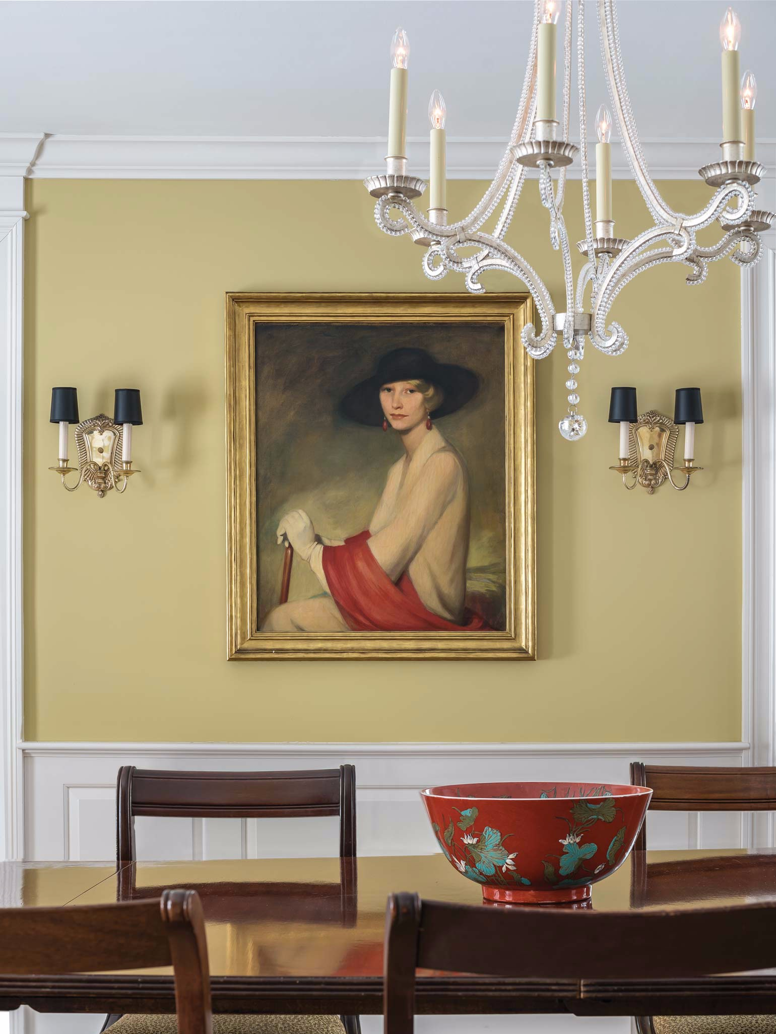 On the wall of the renovated dining room hangs a portrait of Will Ethridge's grandmother, Helen McIntyre, painted by Cecil Clark Davis. A chandelier of Venetian glass, selected by Linda Banks, complements the decor and casts a gentle light.