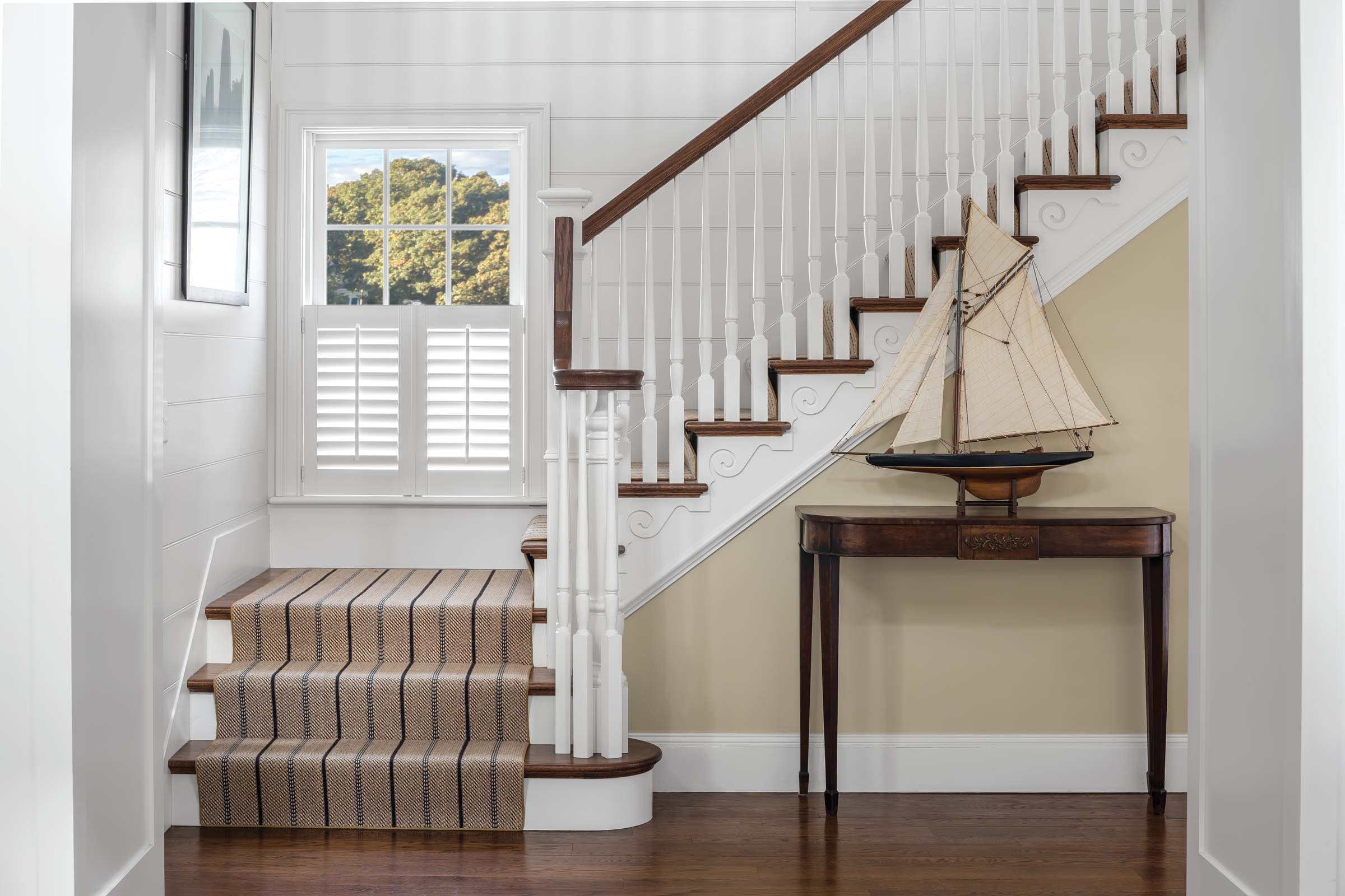 The KA schooner model displayed in the hall interplays with the undulant wave-like molding that runs along the staircase crafted by Brian Sleeper of Period Restoration.