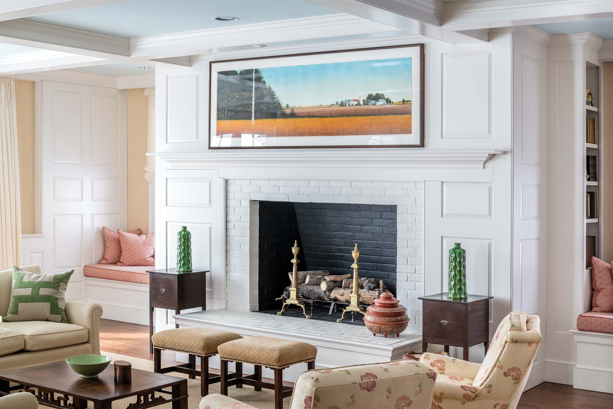 During the living room renovation, architect Gordon Wallace lowered the floor, a design decision that heightened the ceiling and opened up the space while working within the existing structure. The painting over the hearth is by William Dunlap.
