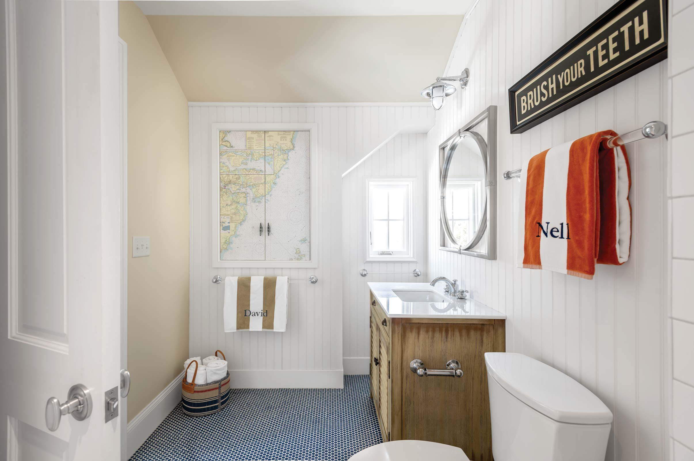 Upstairs in the new wing, a bedroom and bathroom for the Ethridges' grandchildren sports a playful nautical theme. The map on the medicine cabinet features the islands of York Harbor.