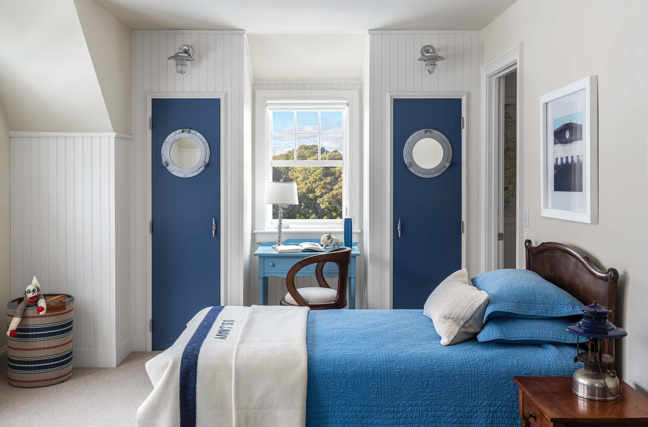 In the grandchildren's room, witty details such as porthole mirrors, ship lights, and boat cleat handles recall a ship's berth. All fixtures and decor are from Simply Home.