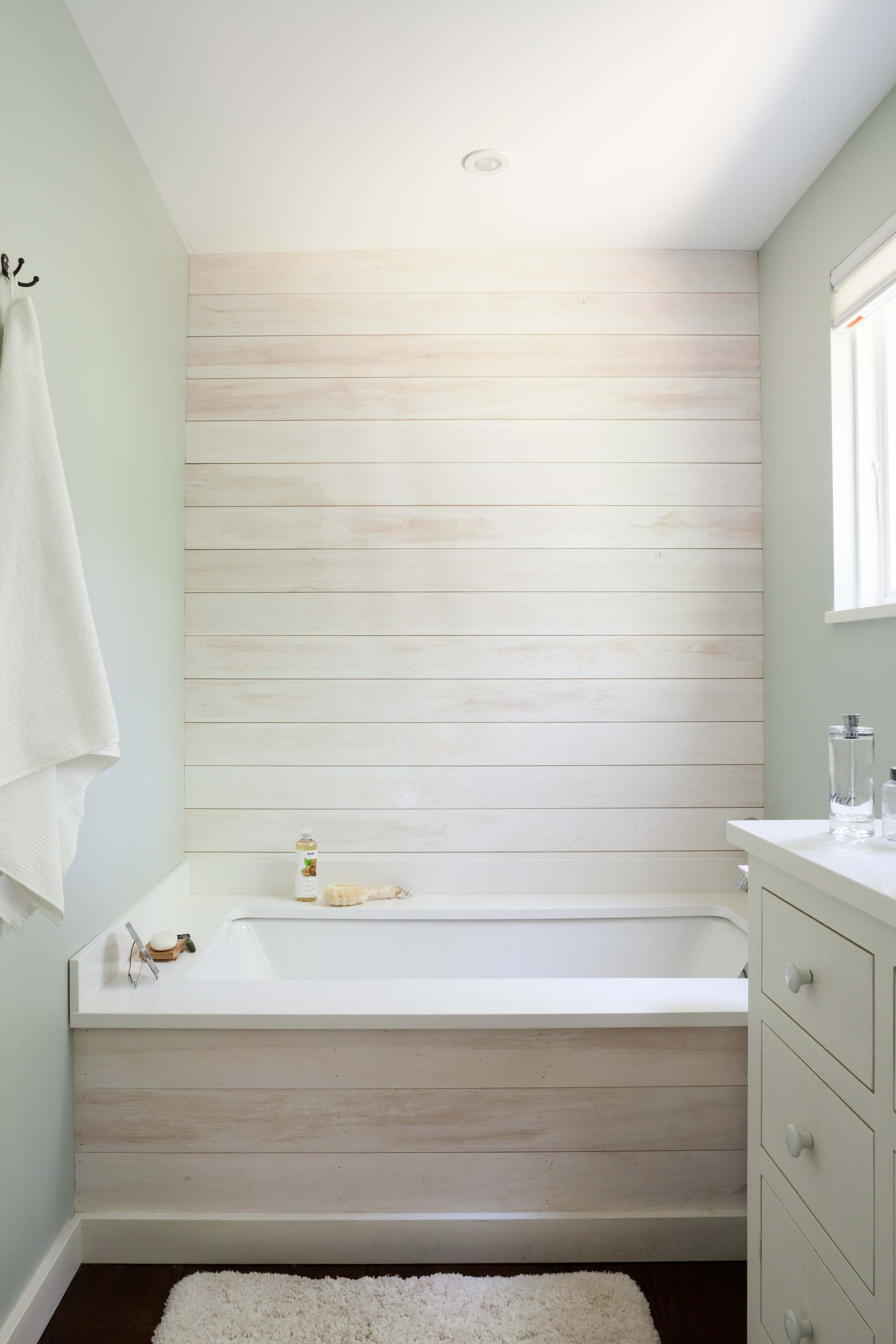 "For the master bath, the boards above and below the tub were whitewashed. The rest of the paint is a Benjamin Moore color called ""Quiet Moment."""