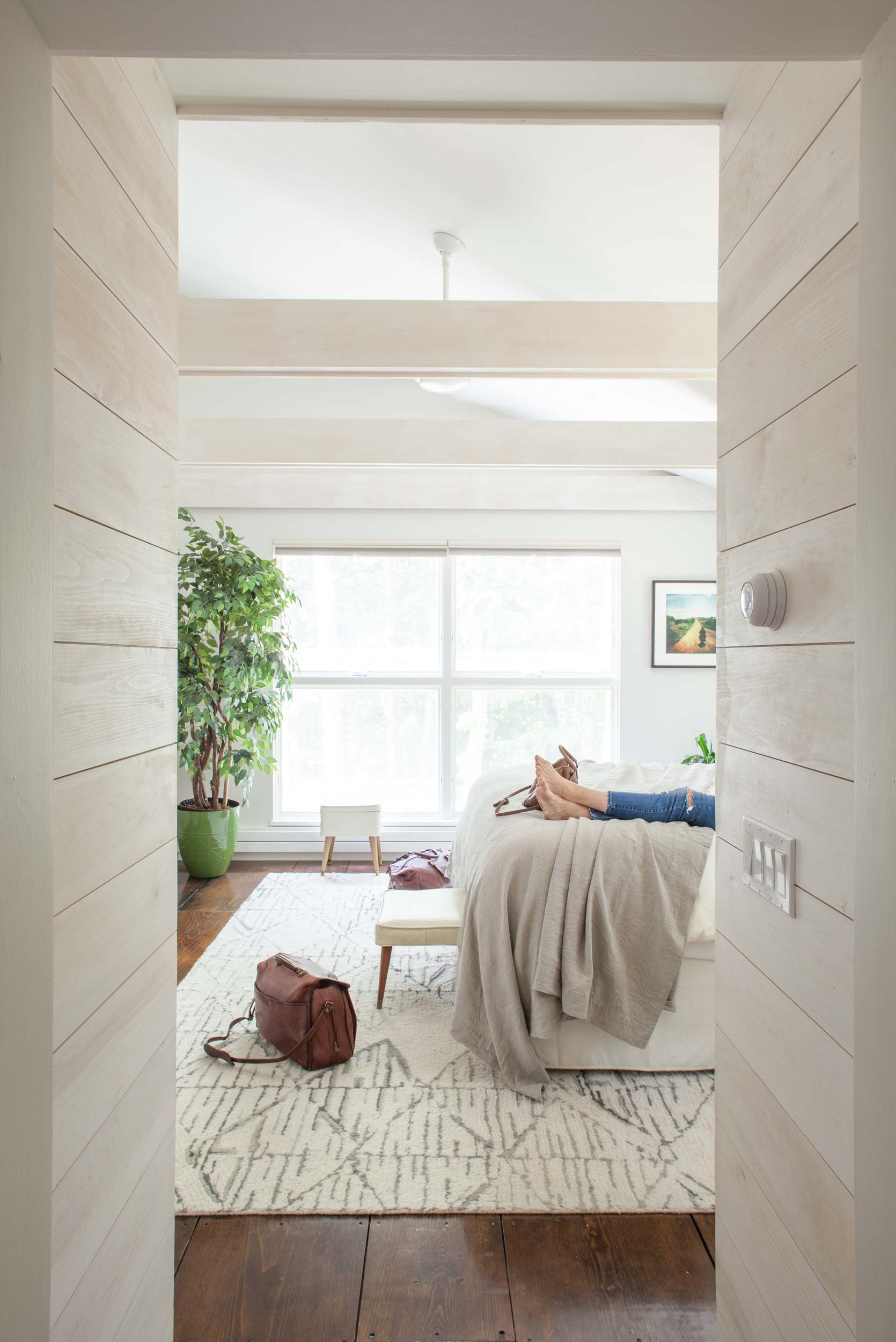 A view into the master bedroom that shows an entryway and beams with whitewash. Here, an original low ceiling was removed to make the space light and airy. The rug is from West Elm. Even the European radiator on the far wall is in keeping with the home's white, clean, and contemporary theme.