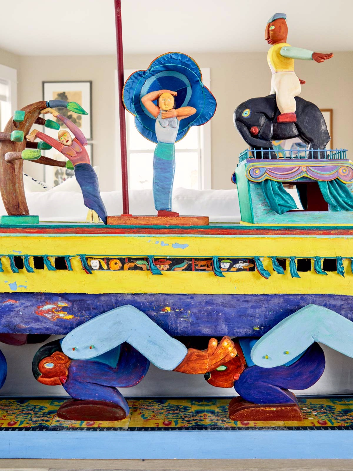 A large, colorful wooden sculpture called  Into the Wind  by Eva Goetz greets you as you enter the living area.