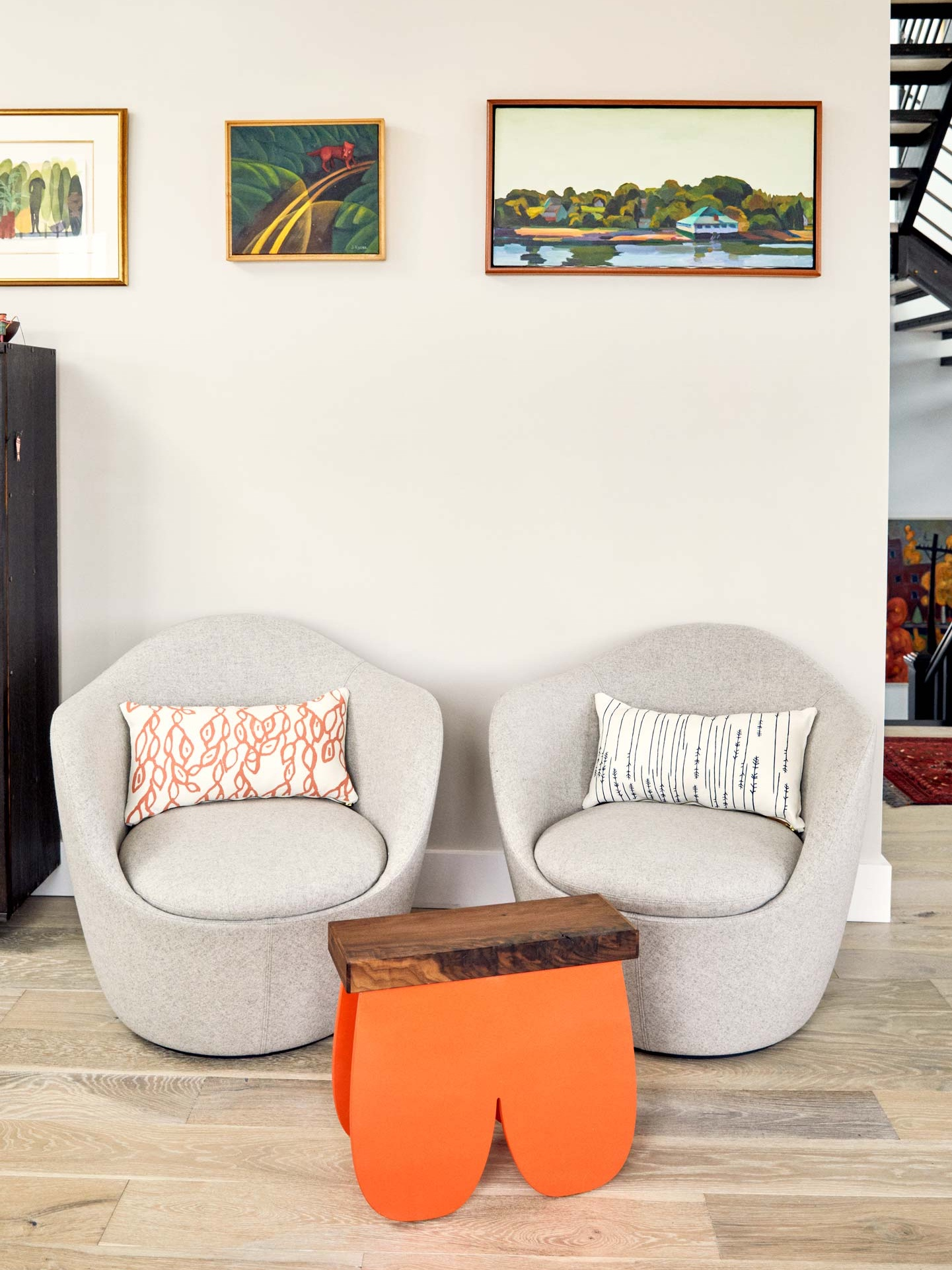 A pair of chairs from Design Within Reach hold pillows by Erin Flett. The shapely occasional table by Peter Dore illustrates Soozie's love for humorous touches.