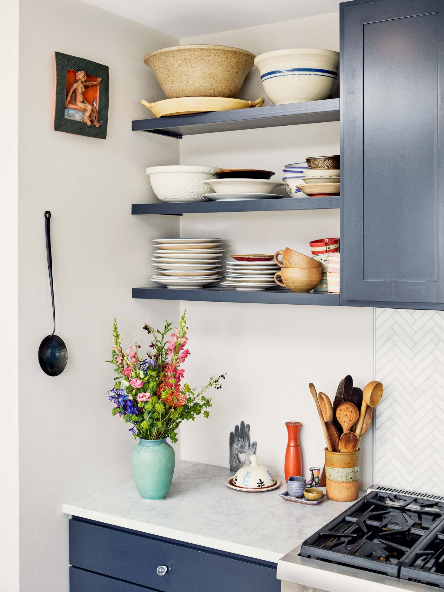 An avid cook, Soozie keeps a collection of well-used spoons in a pottery canister. The marble herringbone backsplash is by Distinctive Tile.