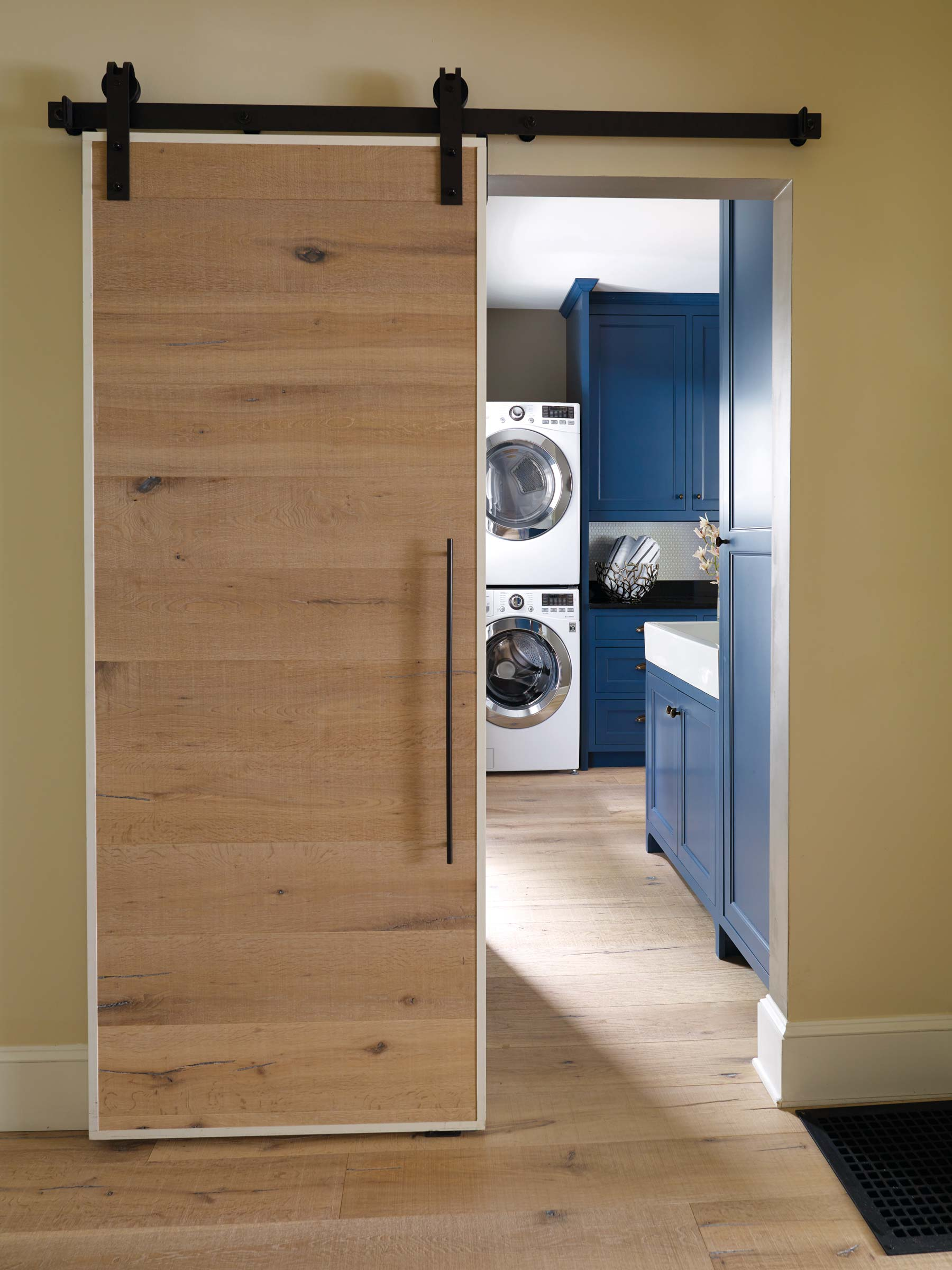 A sliding barn door conceals a butler's pantry turned laundry room.