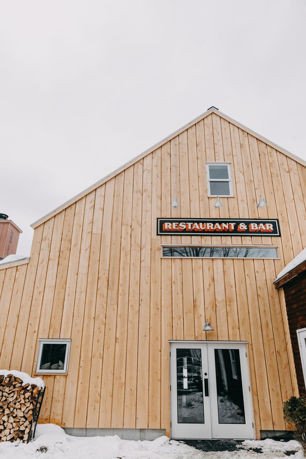 To maintain the exposed wood interior, builder Jesper Kruse of Maine Passive House insulated the building from the exterior. To the right, the bottle shop offers a small tasting area, beers to go, and Oxbow merchandise.