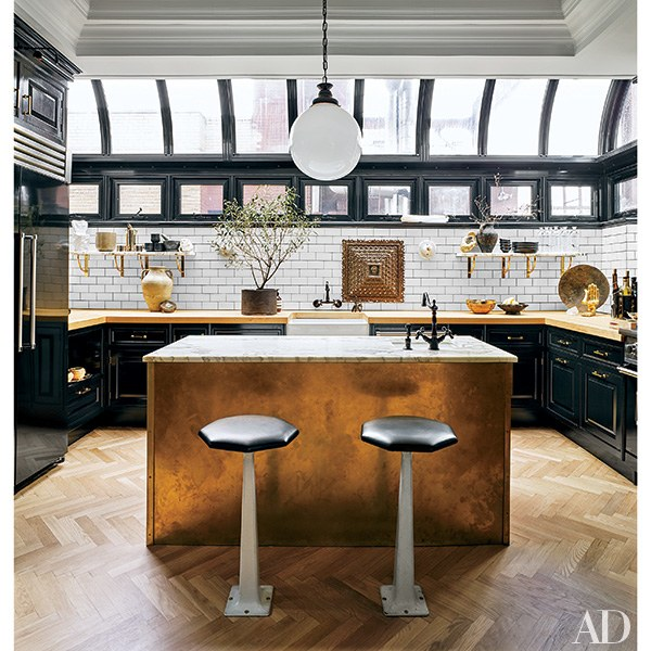 Nate Berkus's kitchen featured in Architectural Digest— I love that he put a picture light over the upper cabinet, above the fridge.