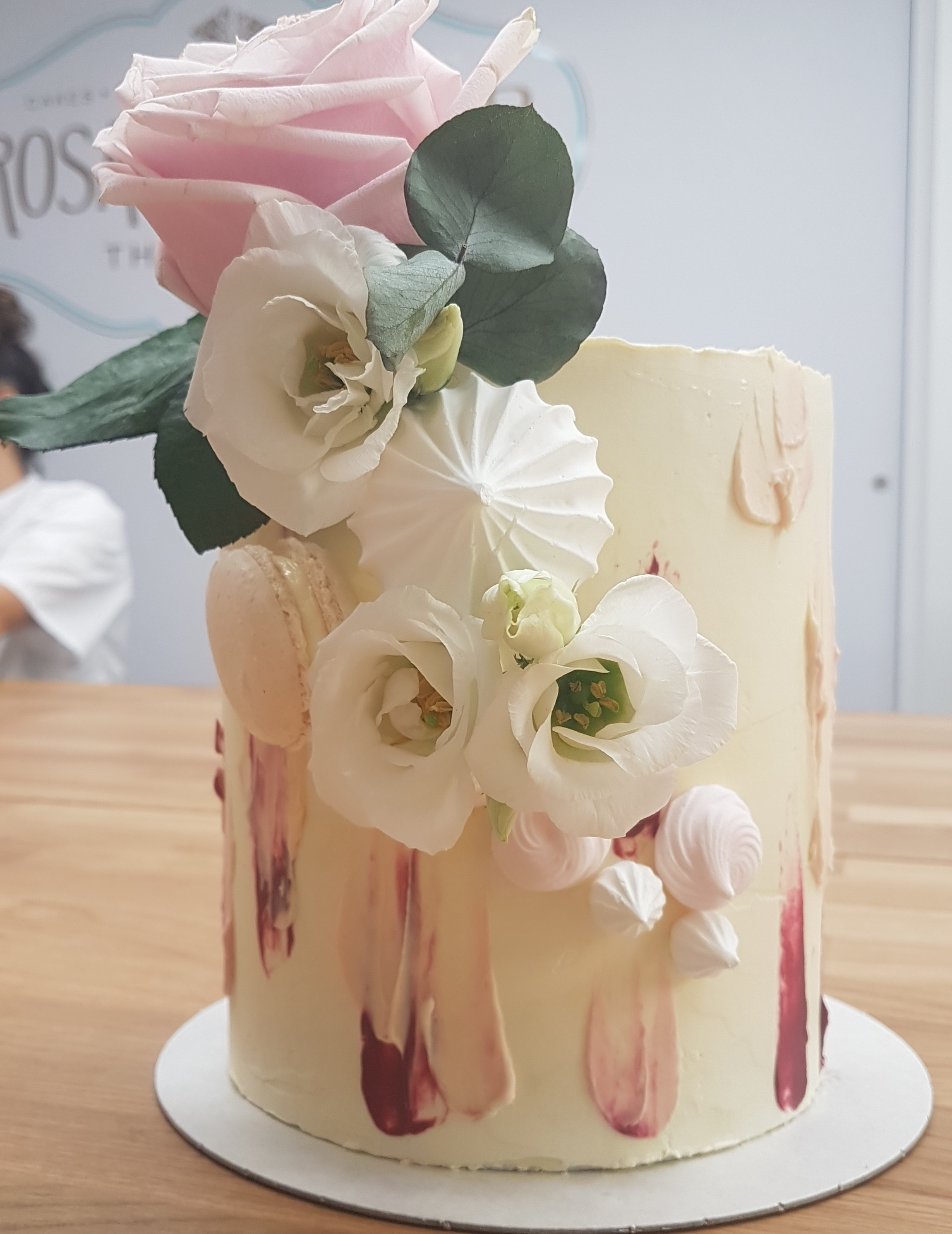 A tall vanilla and raspberry cake with watercolour buttercream