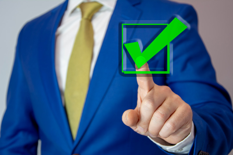 business man touching check mark on virtual screen with left hand
