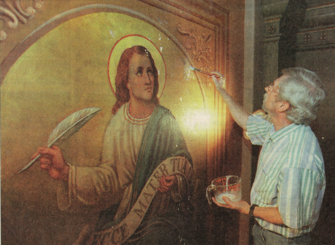 Painting conservator Jerry Litmer applies a coat of preservative adhesive to the wall-mural image of St. John.