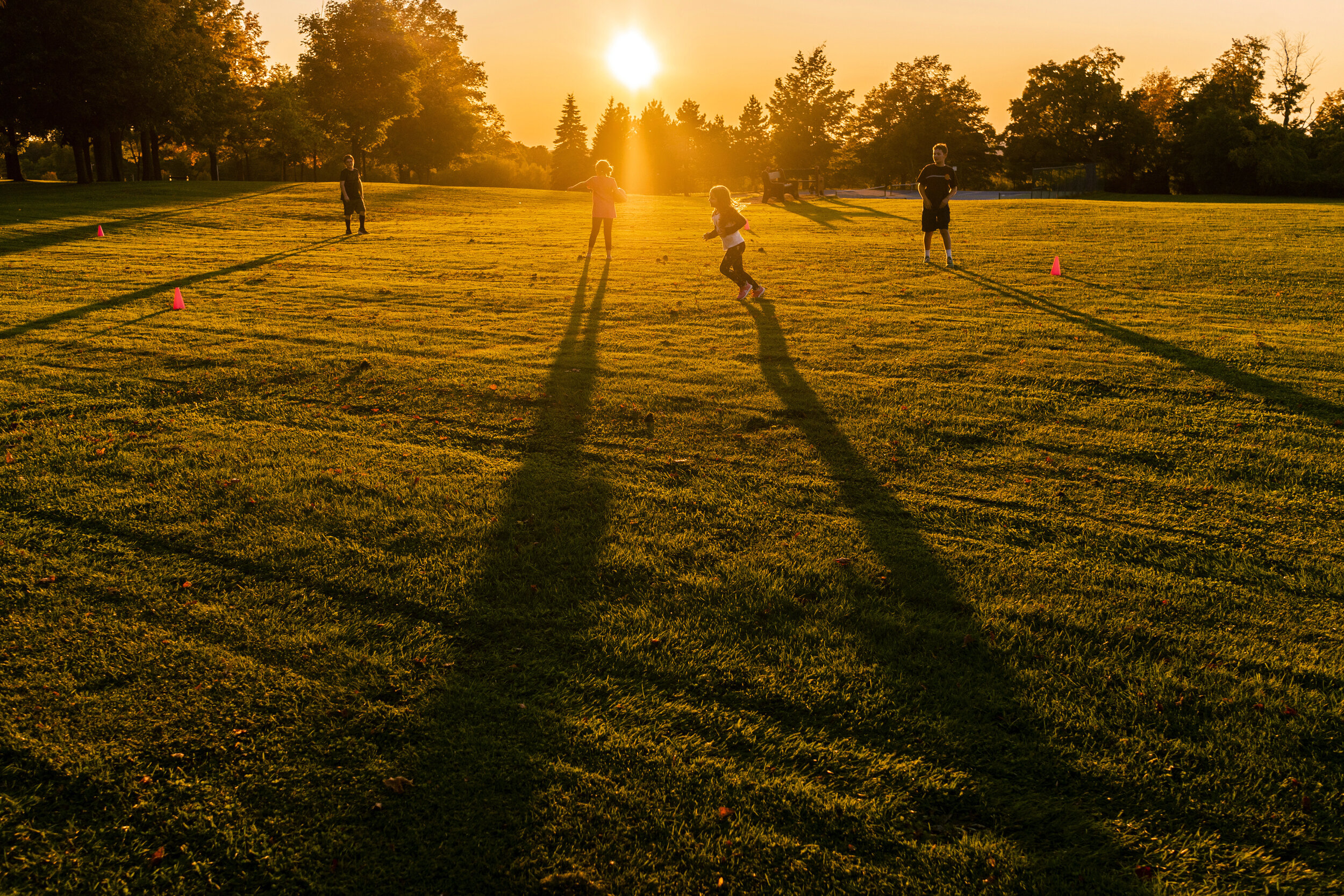 Long shadows stretch across the field as, from left to right, Connor Lamica, 10, Flora Bates, 9, Kate Lamica, 6, and Nicolas Bates, 12, play kickball at Thompson Park.