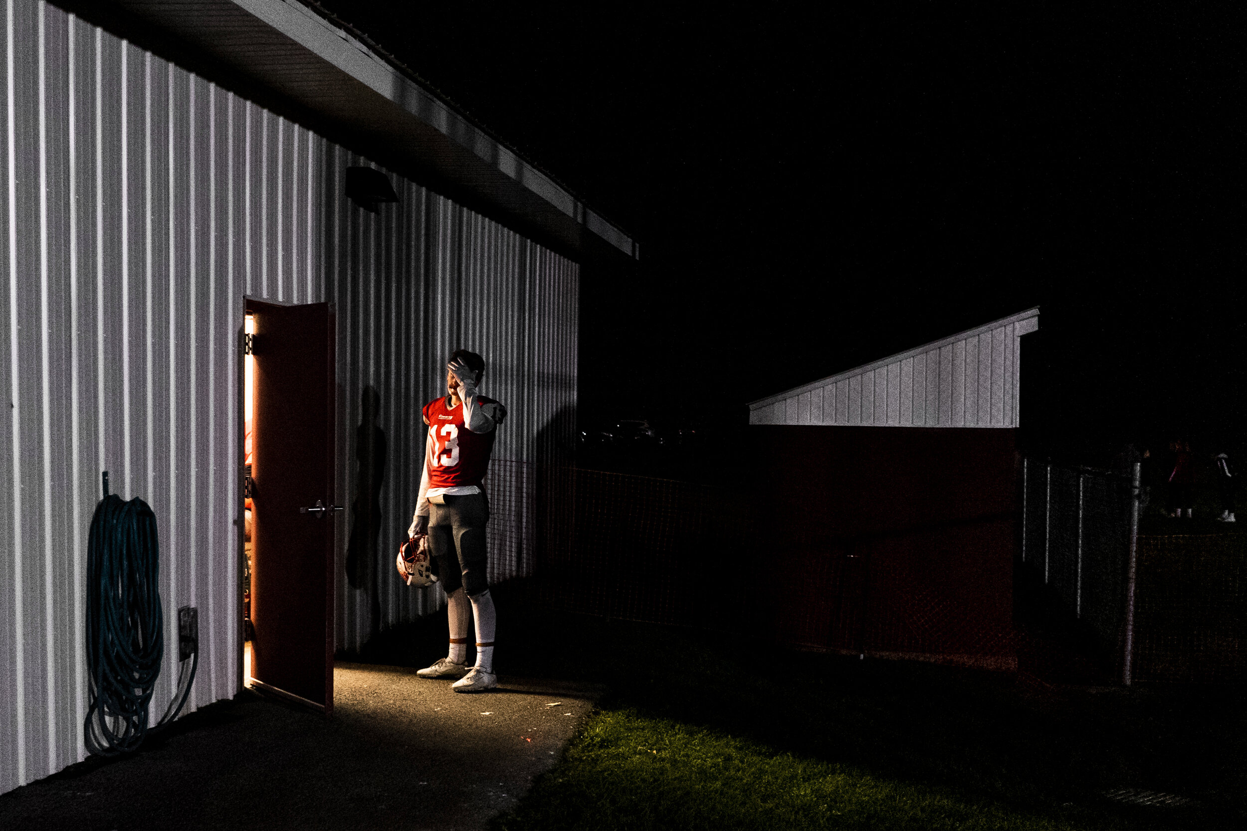 Thomas Albright, of Carthage Football, steps into the beam of light from the open door of the locker room during halftime of their game against Indian River at home in Carthage, NY.