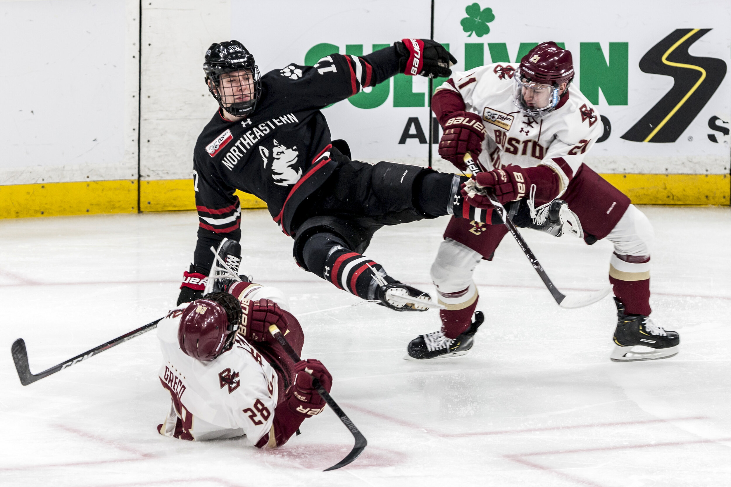 Austin Goldstein, of Northeastern University Men's Hockey, is caught mid-air between two Boston College defenders during the 2019 Beanpot Final at TD Garden in Boston, MA.
