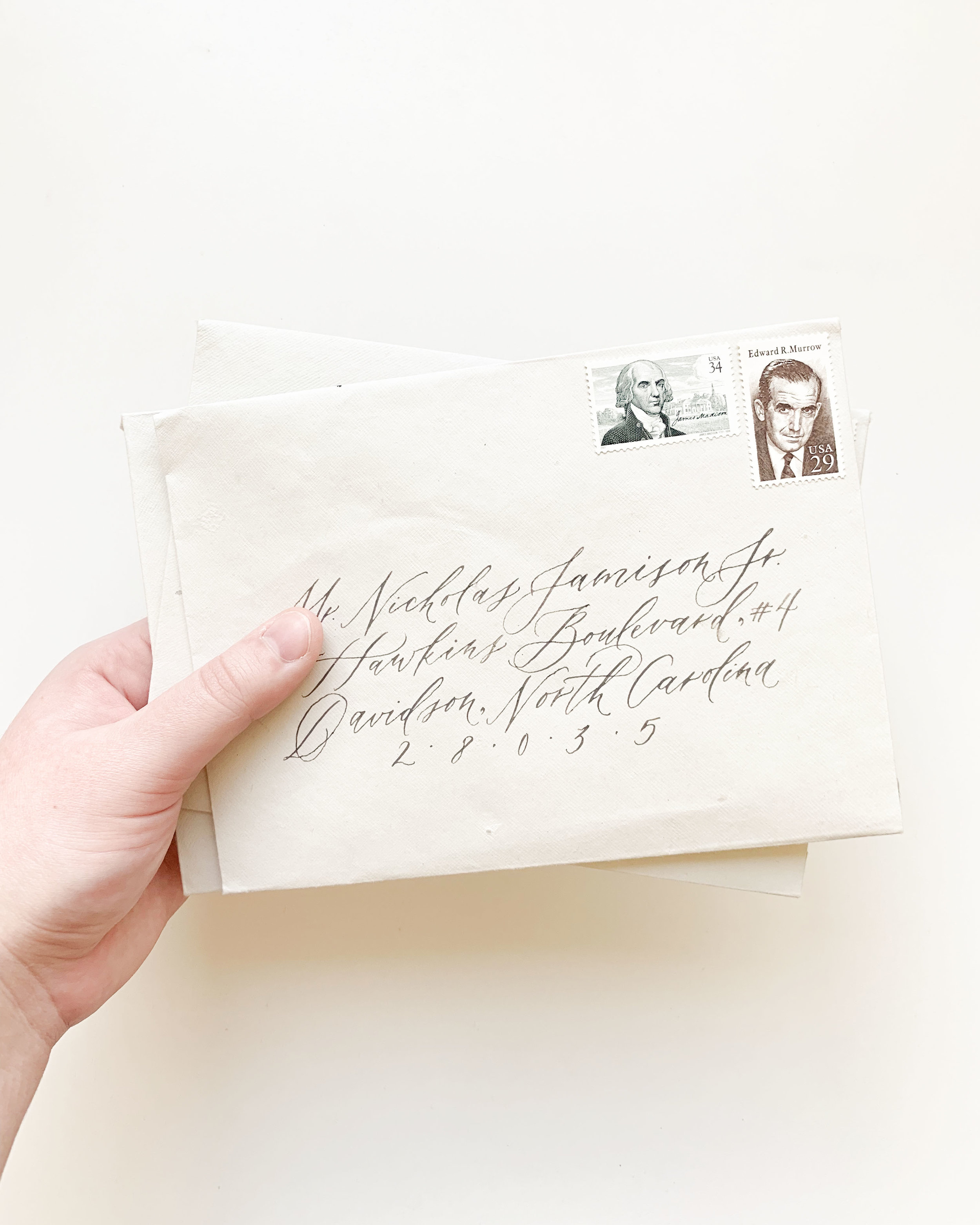 Vintage postage, calligraphy addressing, and handmade paper envelopes for custom fine art wedding invitations.