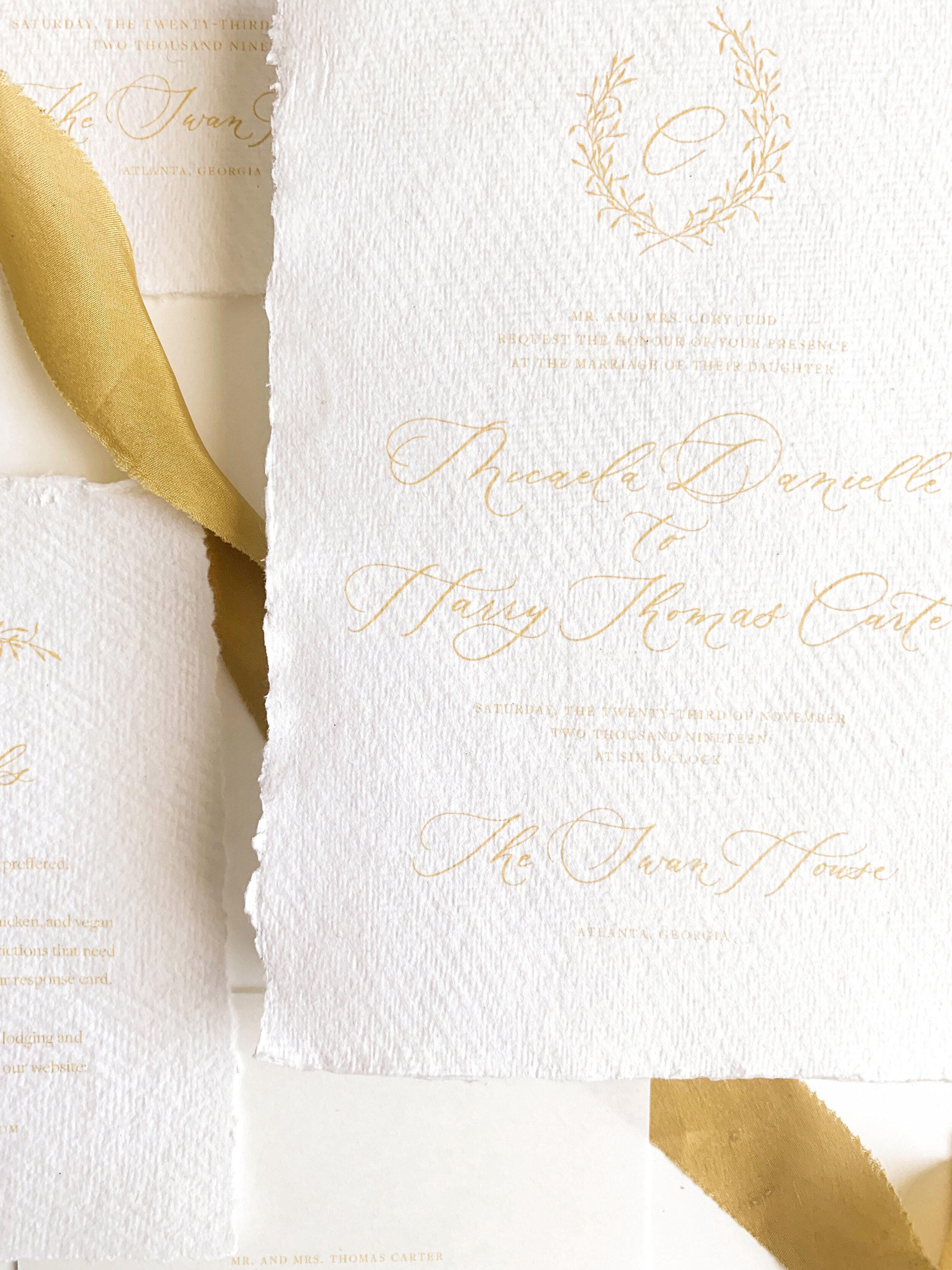 Elegant traditional wedding invitations. Gold and blue wedding invitations on handmade paper. Monogram crest calligraphy wedding invitations. Ribbon wedding invitations