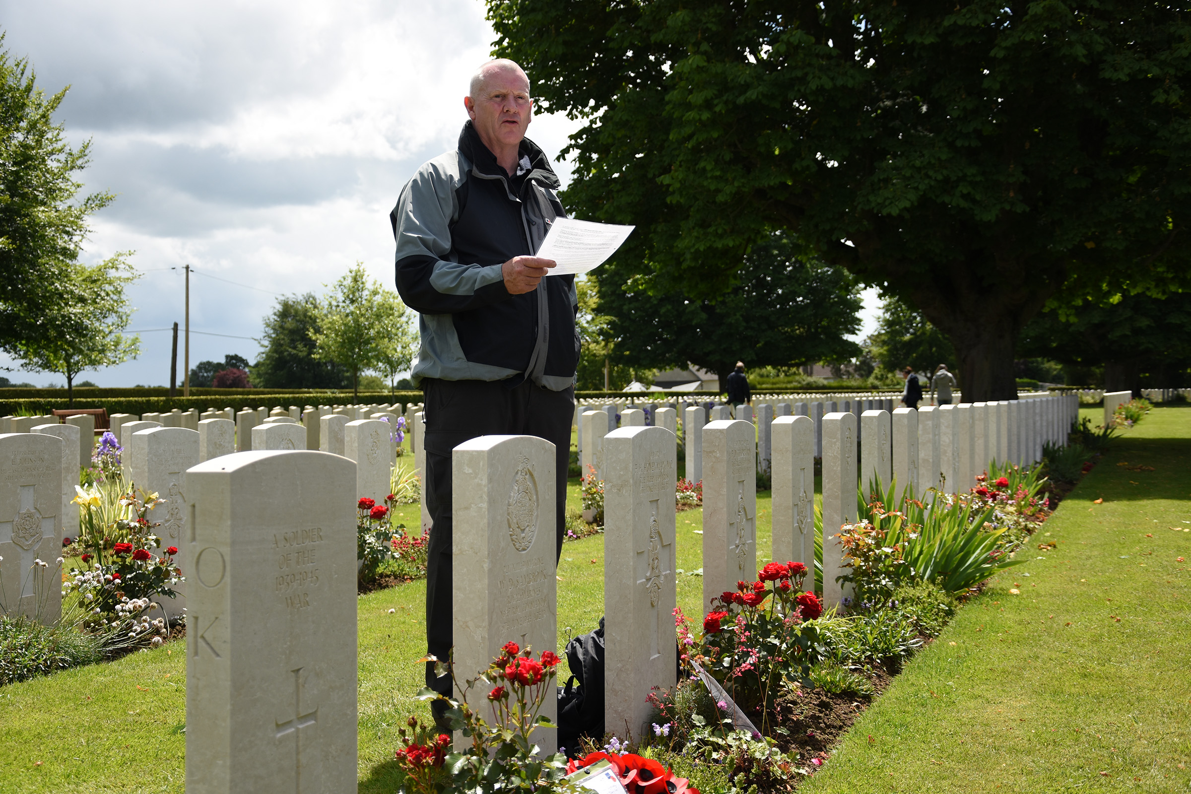 Capt. Shaun Mallinson , stood at the graveside of Maj. Lofthouse, OC of 6th Battalion The Green Howards, on D-Day
